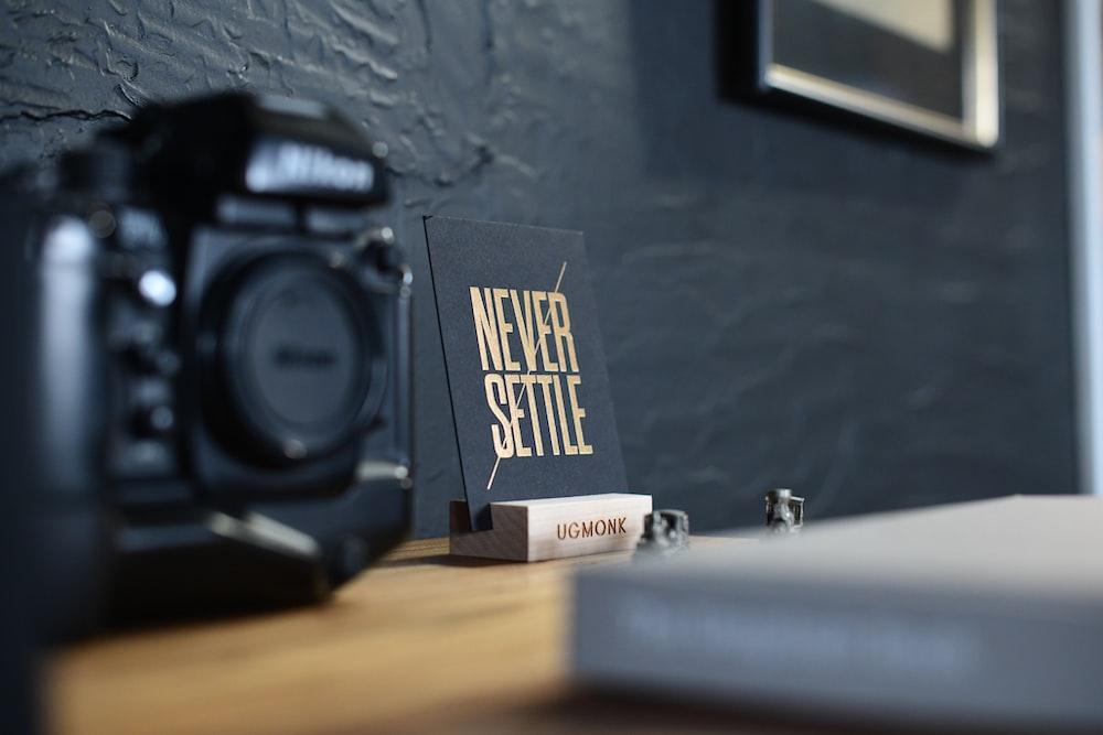 black Nikon DSLR camera beside decor