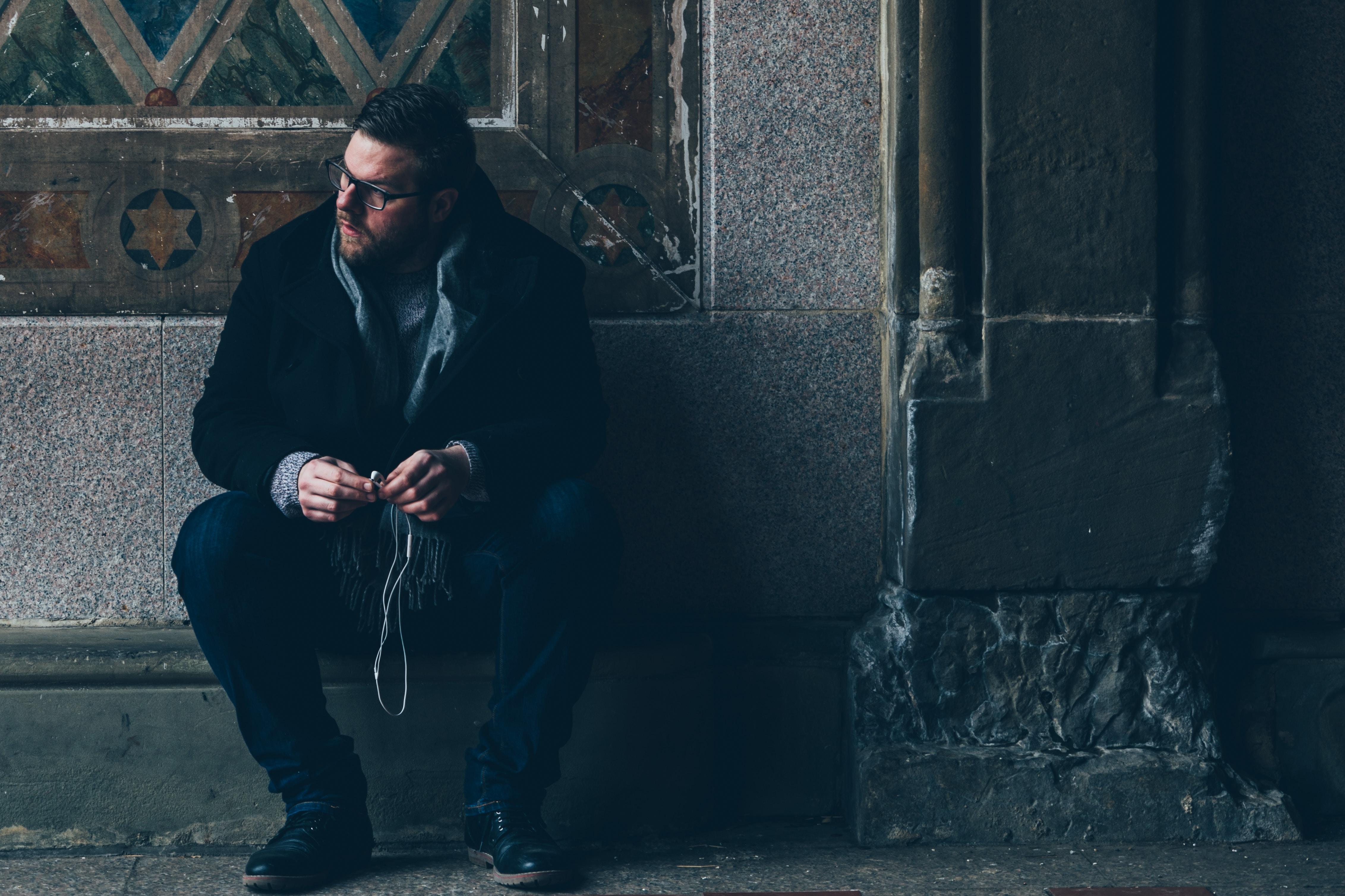 man sitting on pavement on vignette photography