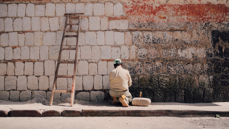 man in beige dress shirt sitting on wall