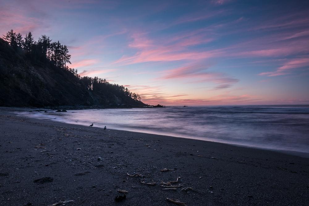 silhouette of mountain in seashores