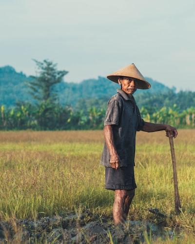 man holding pickaxe in grass field