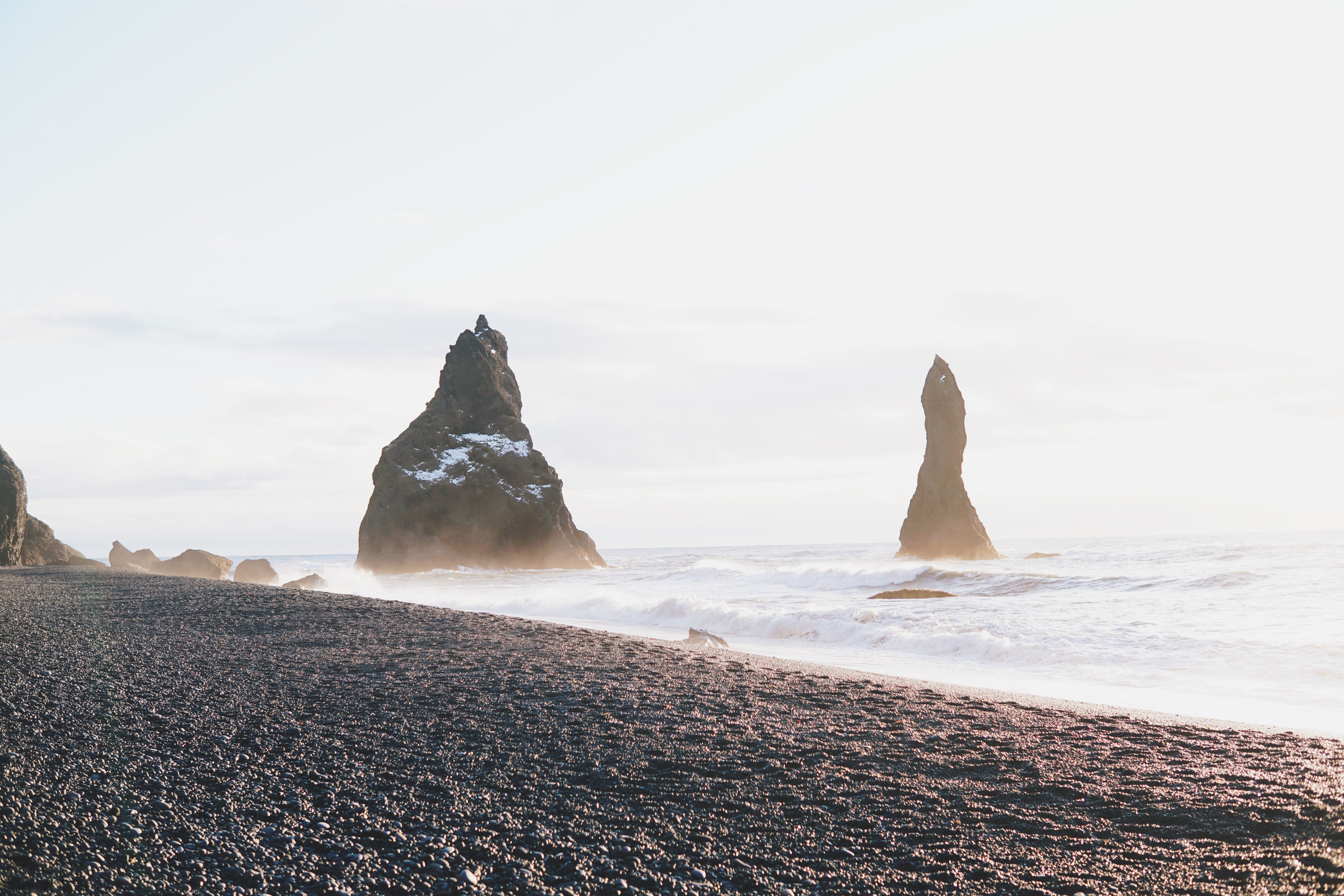 two black rock formations near shore at daytime
