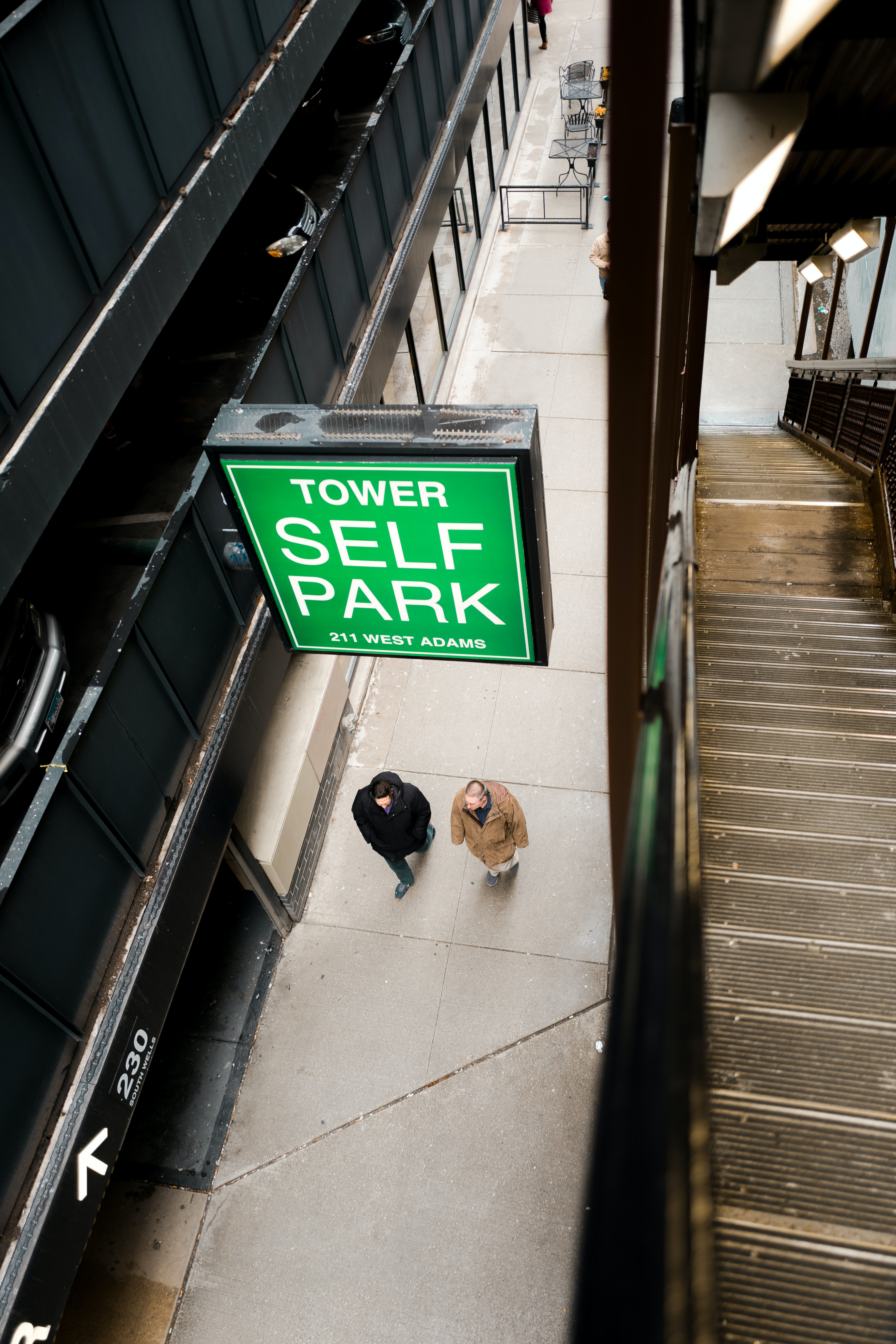 two person's walking underneath Tower Self Park signage