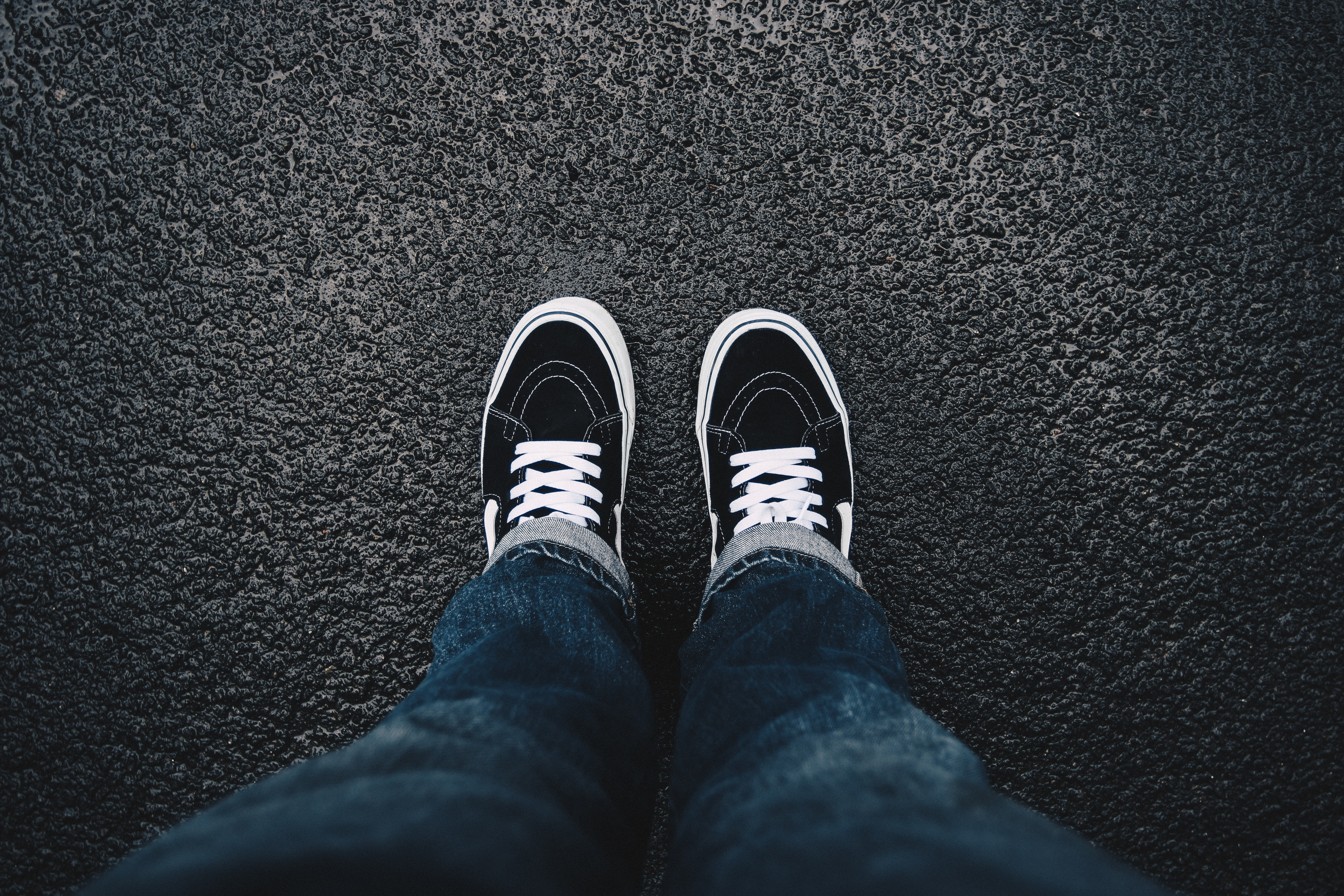 person wearing black sneakers standing on black surface