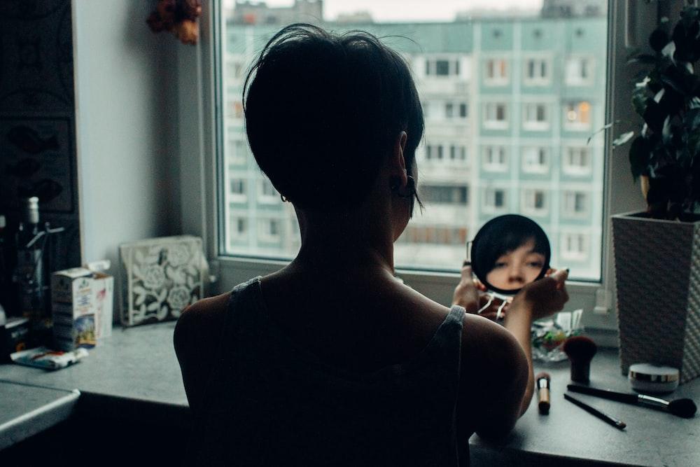 woman looking at mirror beside window