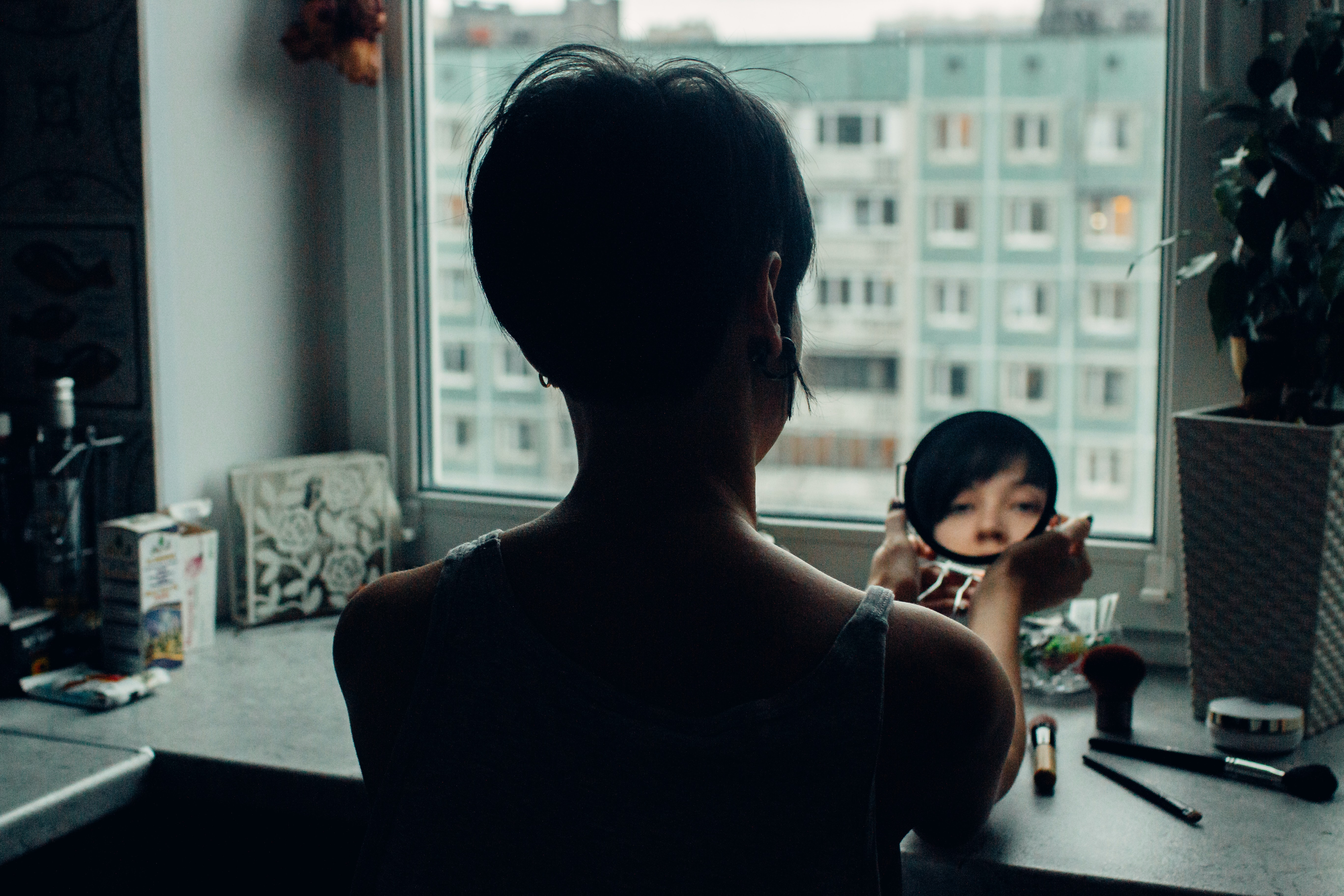 woman looking at mirror beside window