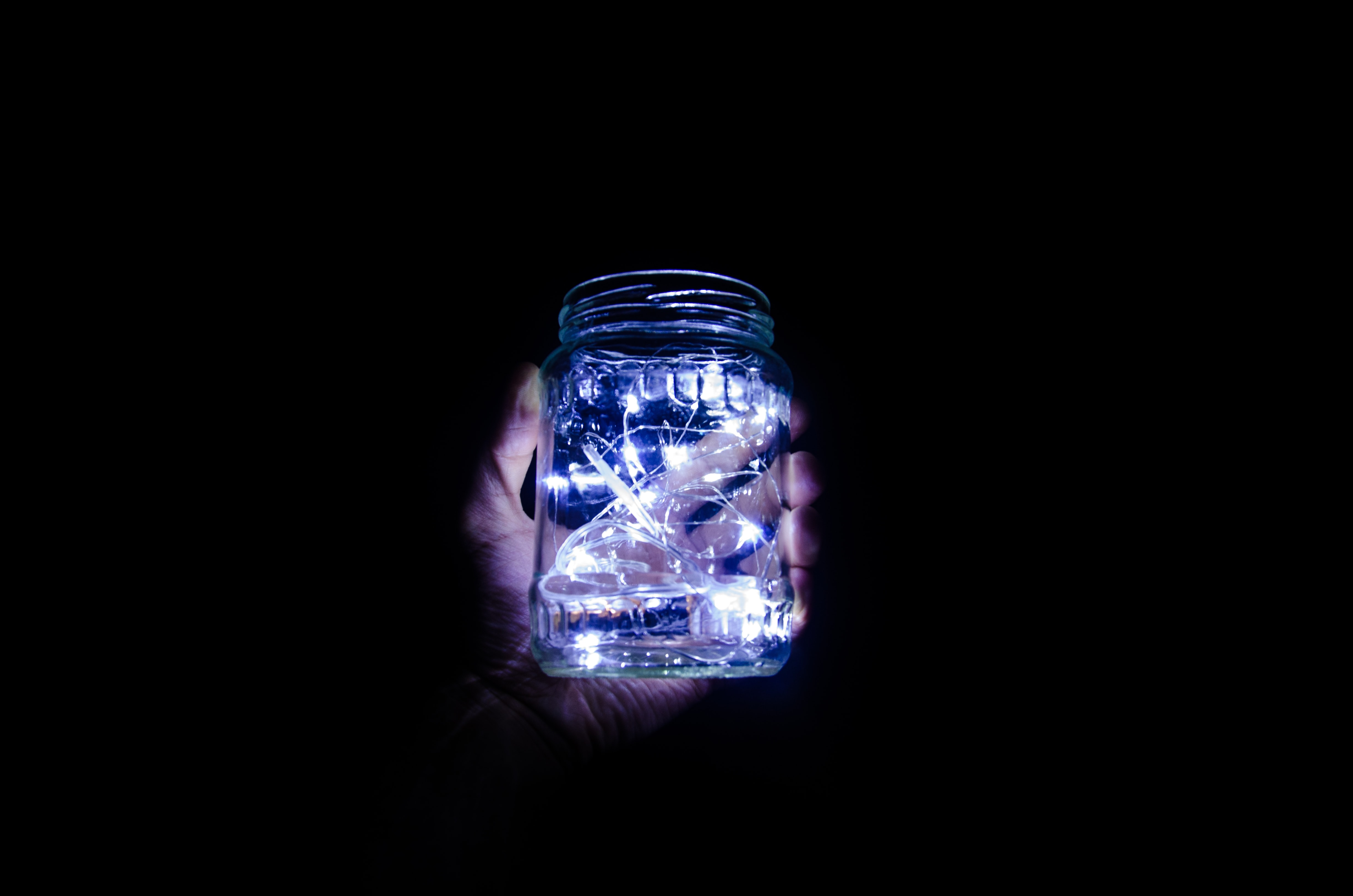 person holding jar with string lights