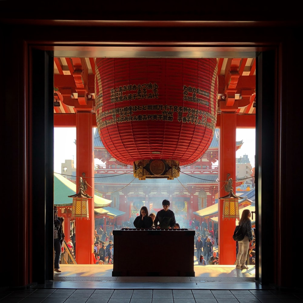 two person standing on altar praying inside temple