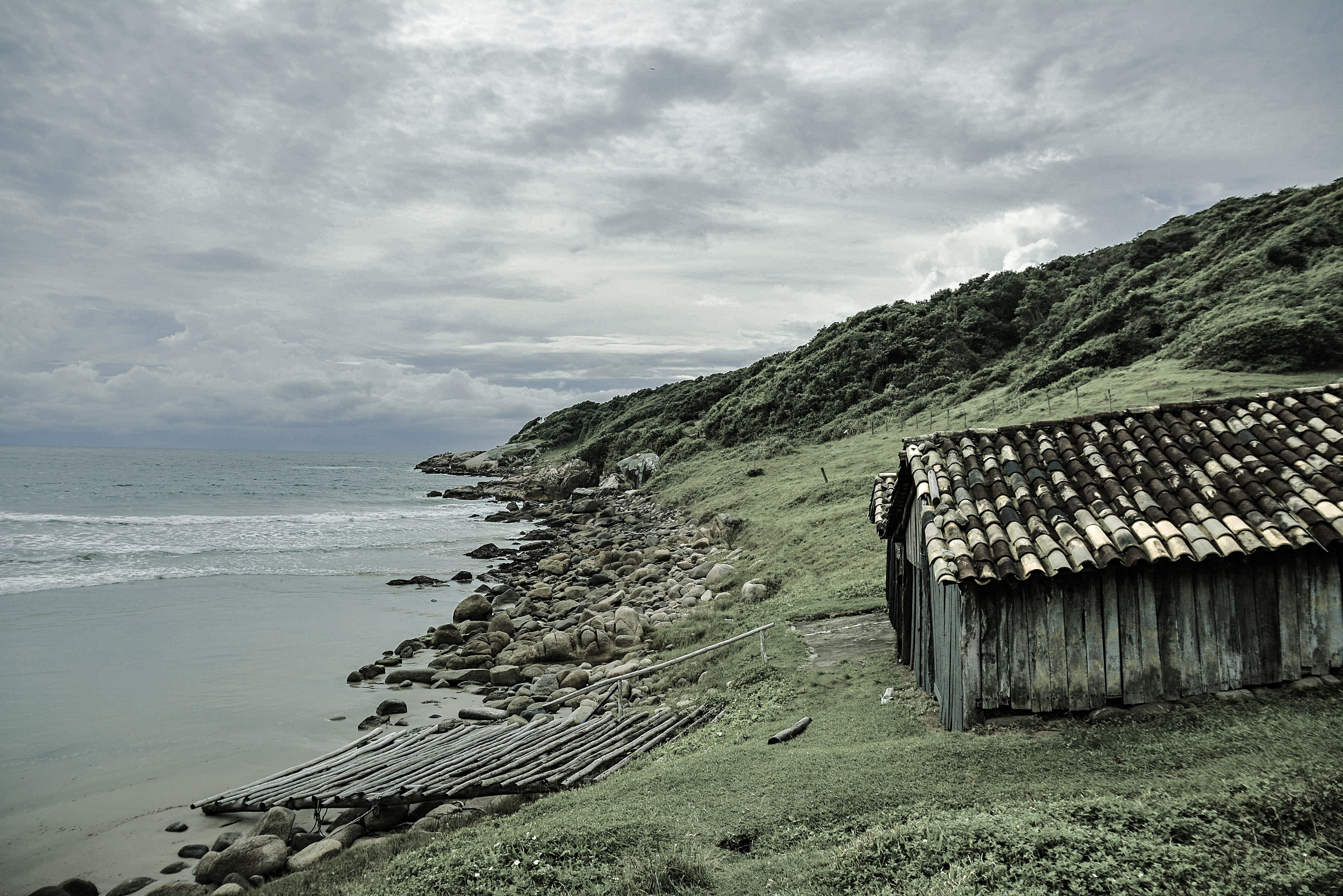 brown house beside ocean under cloudy sky during daytime