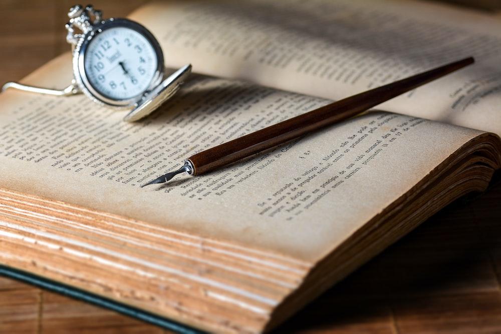 brown pen on top of book beside gray pocket watch