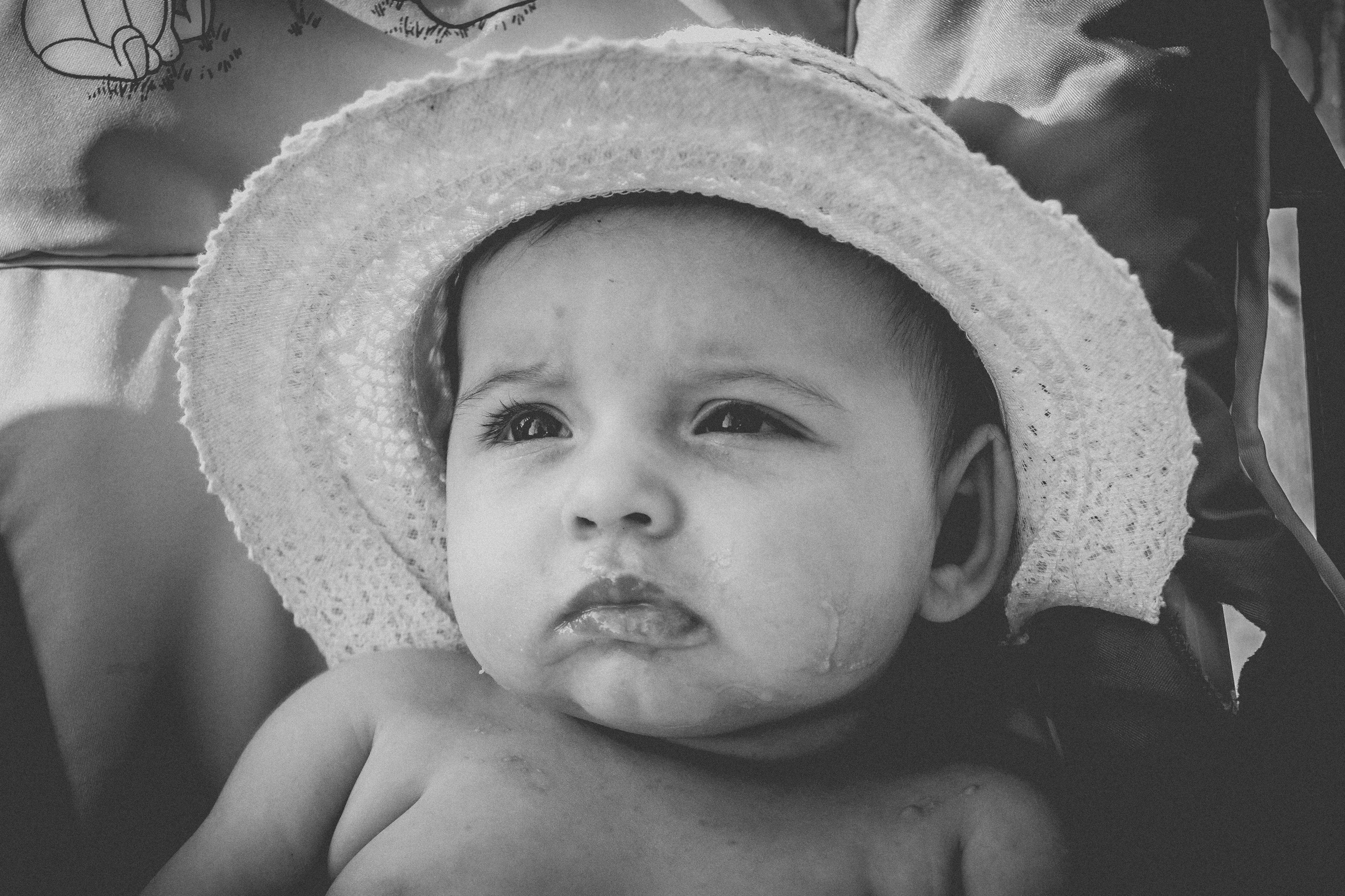 grayscale photography of baby wearing hat