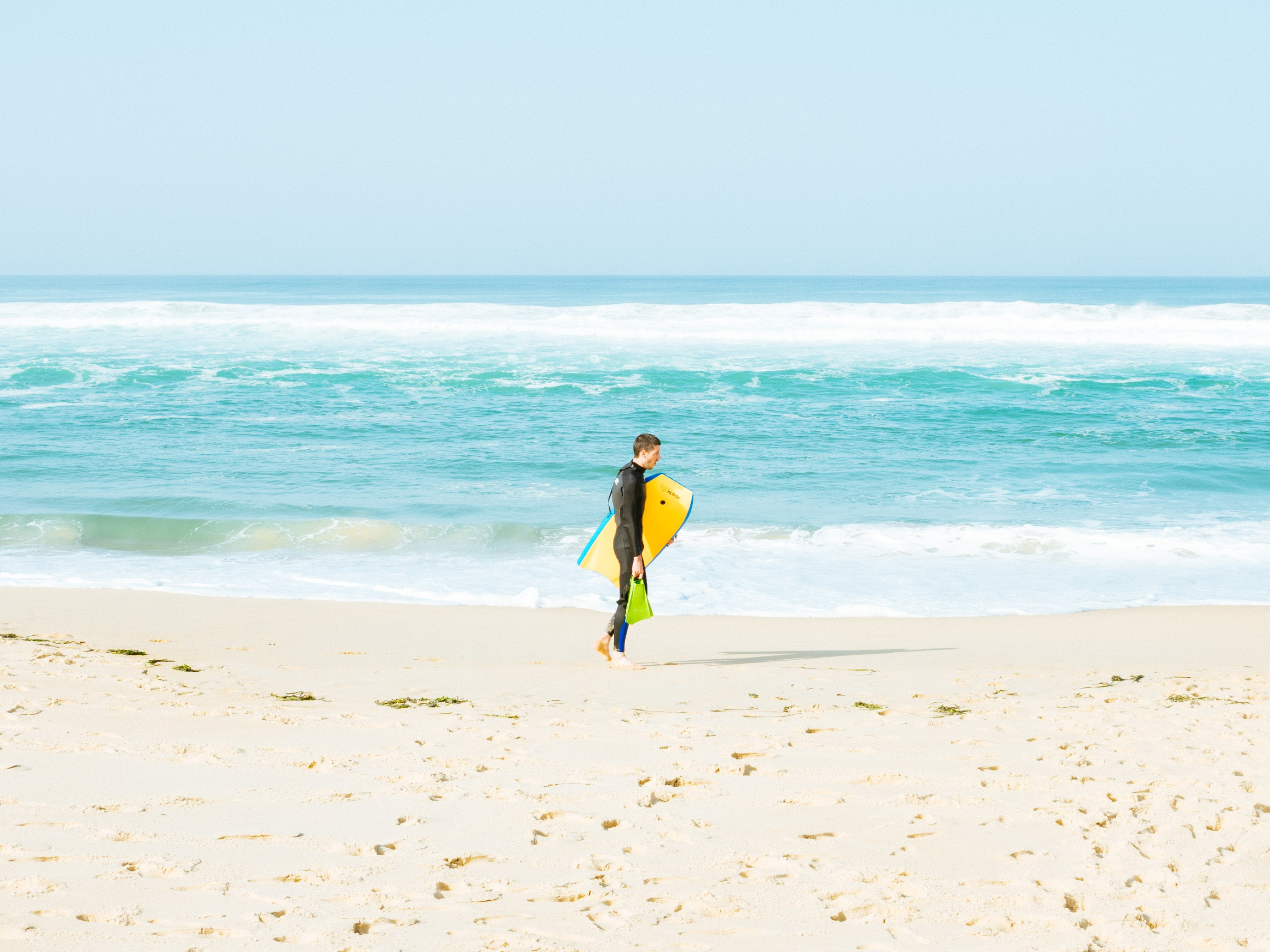 man walking on seashore holding yellow surfboard