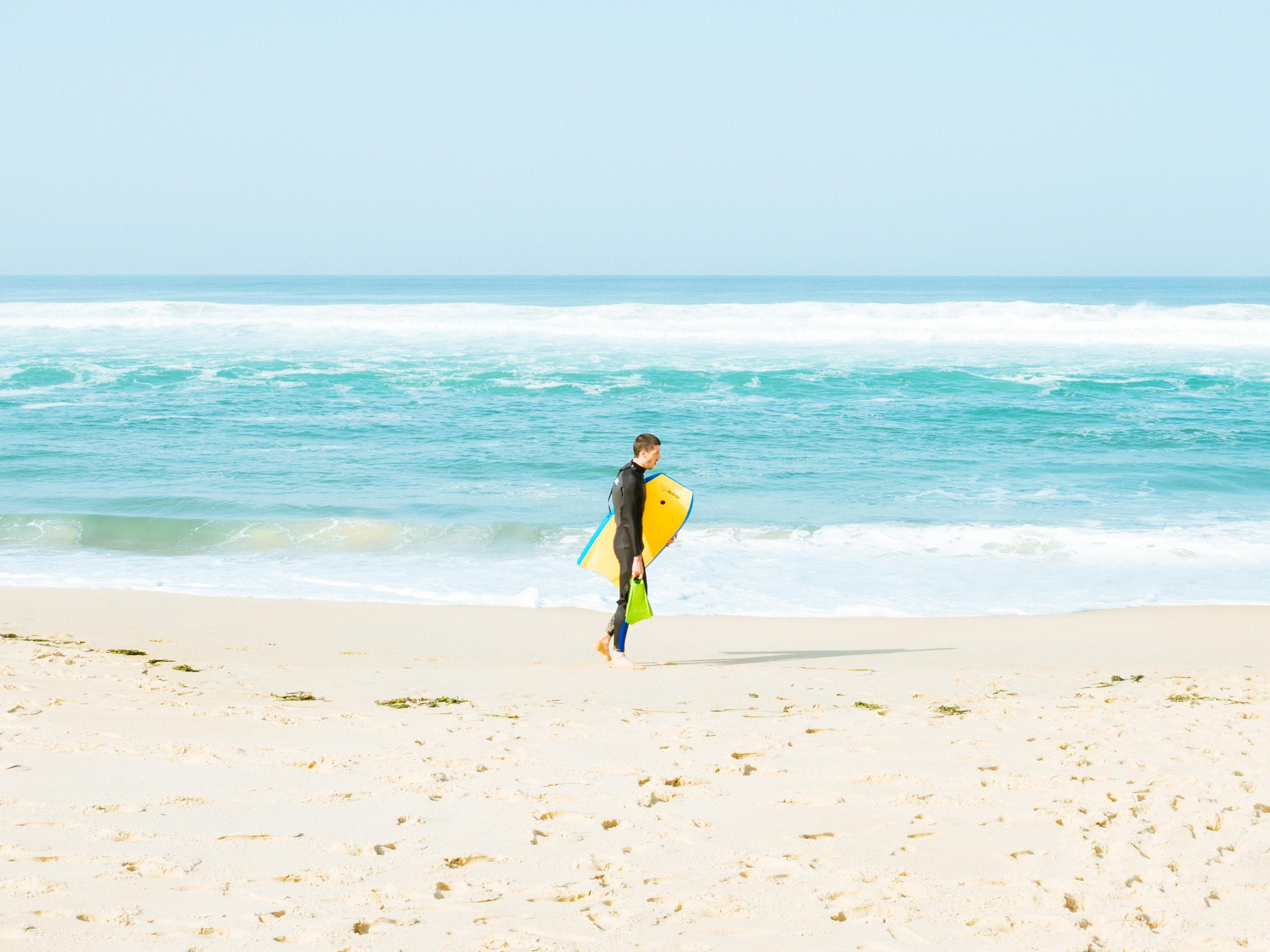 man walking on seashore holding yellow surfboard