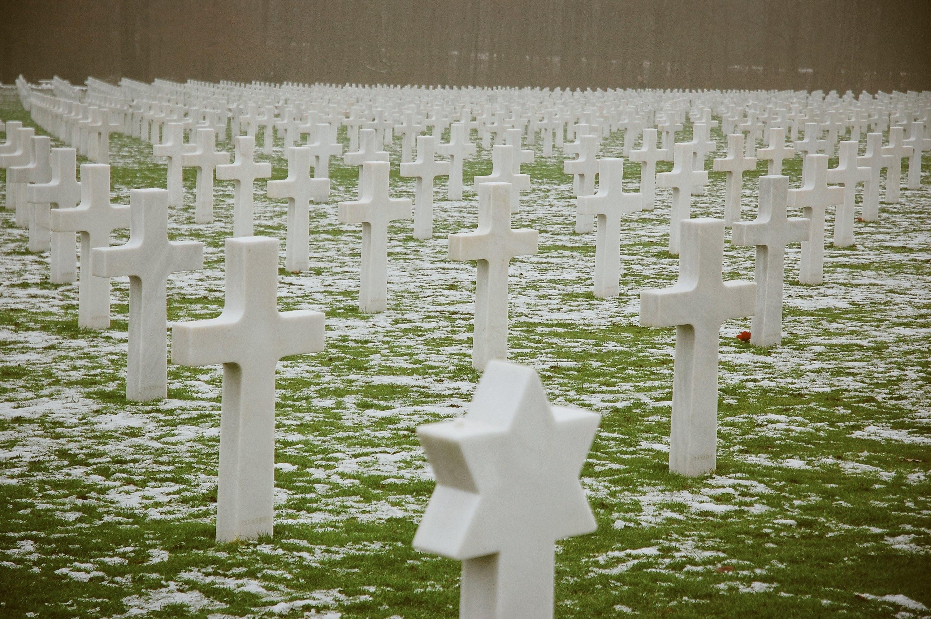 white concrete cross tomb on green grass field