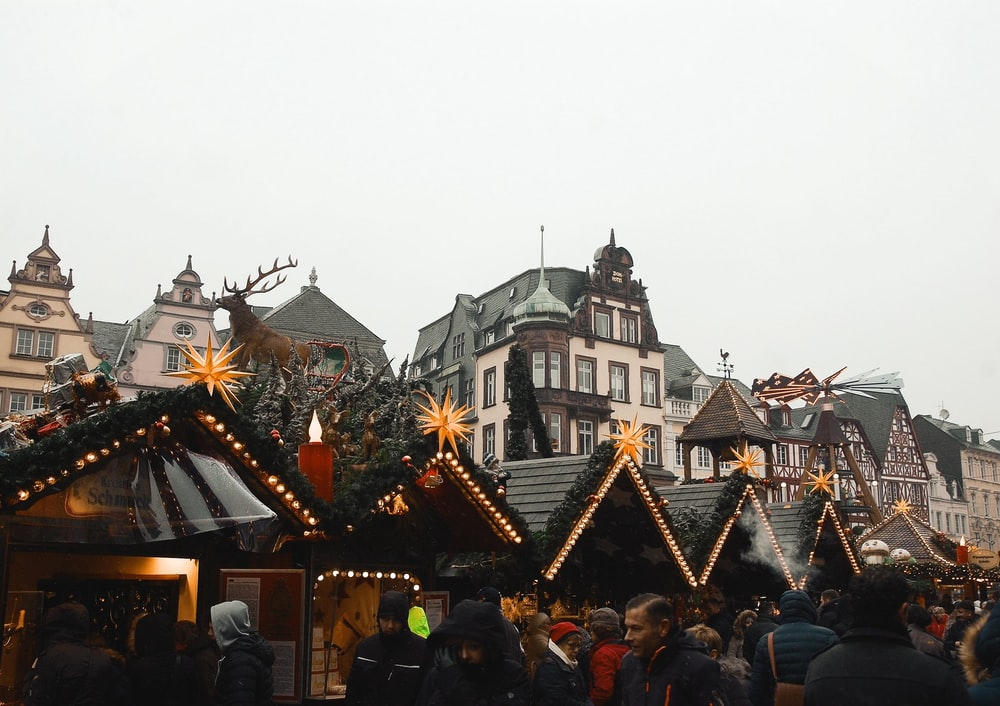 people passing by black and brown wooden structures