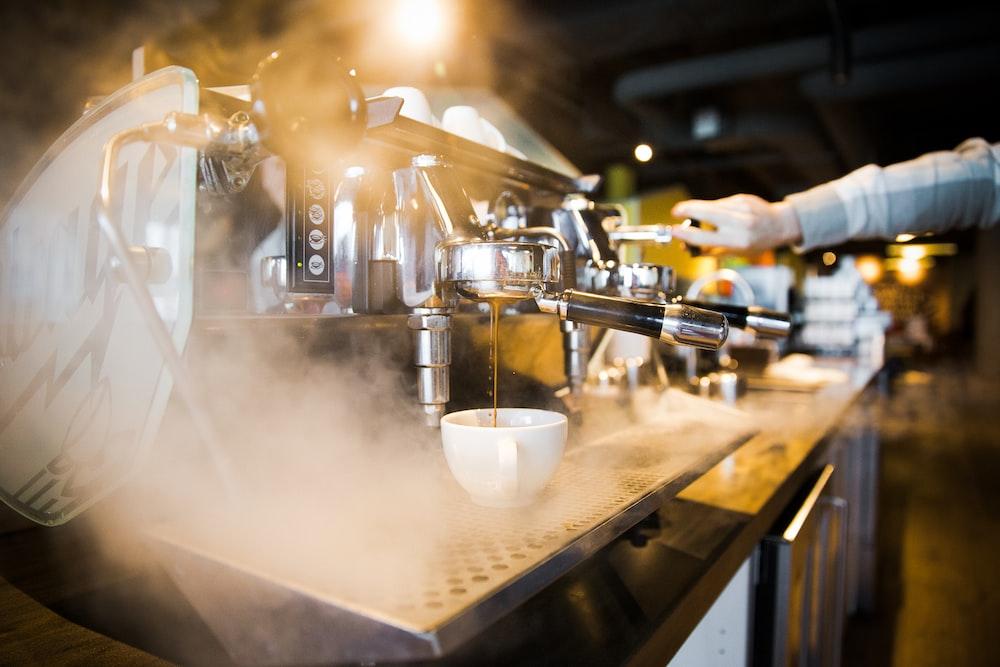 person pressing espresso maker during night