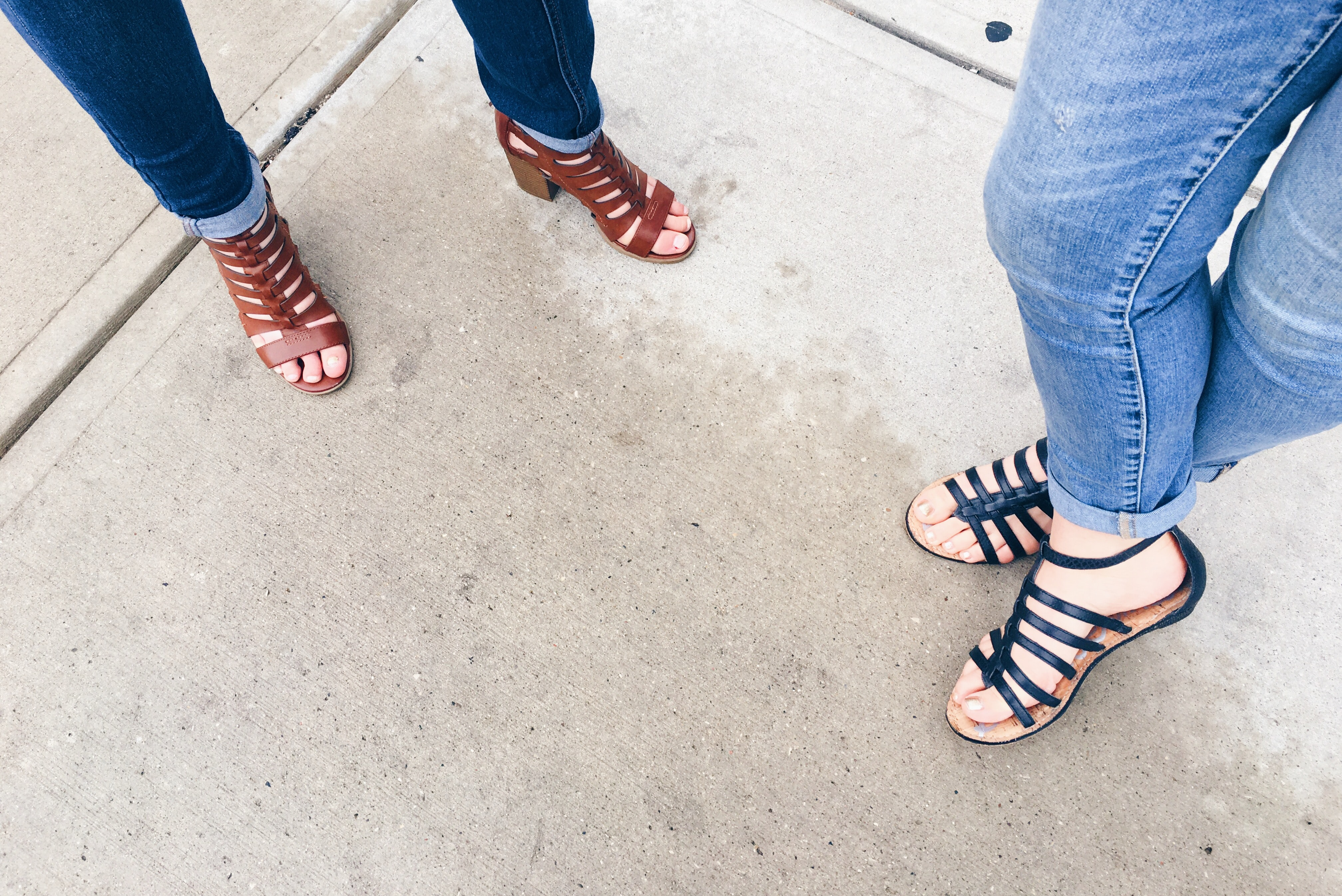 two woman wearing black and brown strappy sandals