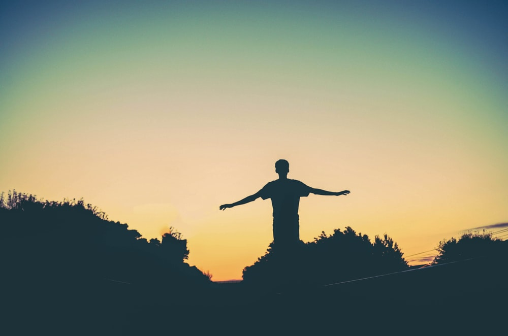 silhouette photography of man raising arms