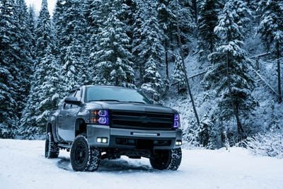 gray pickup truck on snow field surrounded by trees vehicle teams background