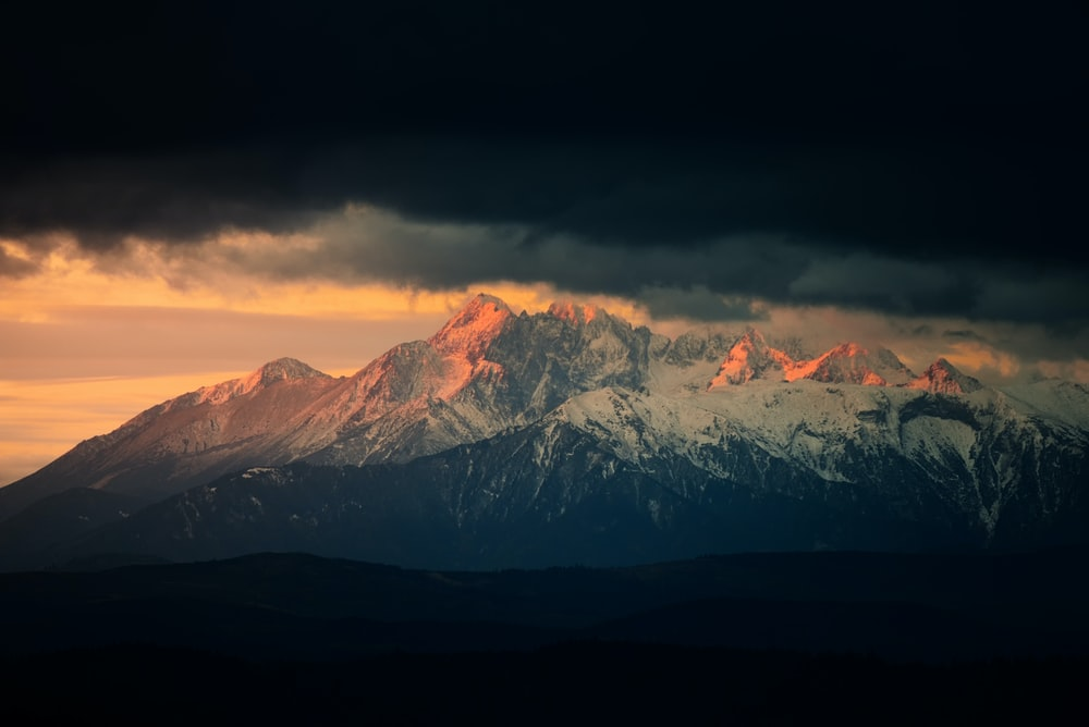 landscape photography of snow mountains under nimbus clouds