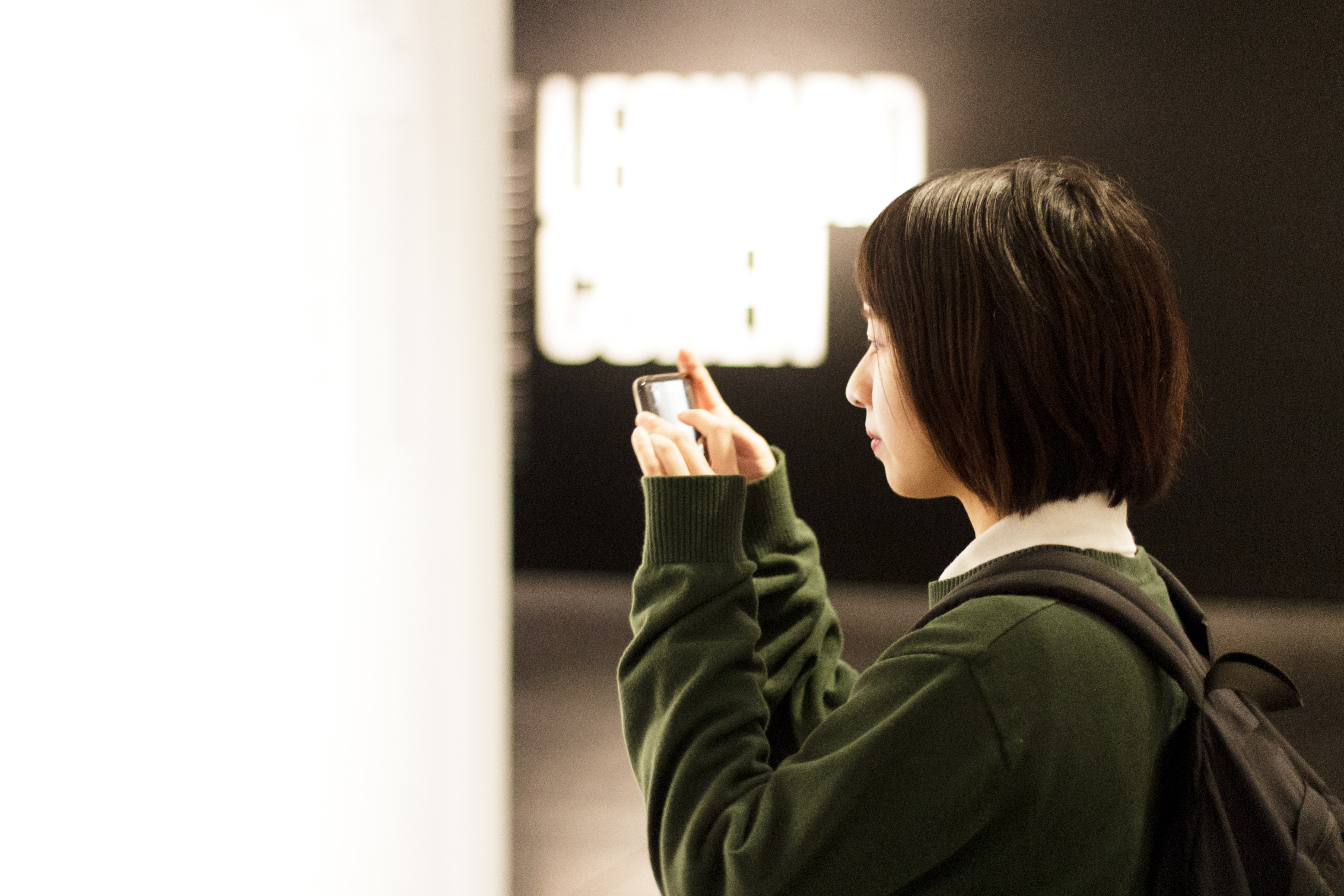 woman holding smartphone while taking picture