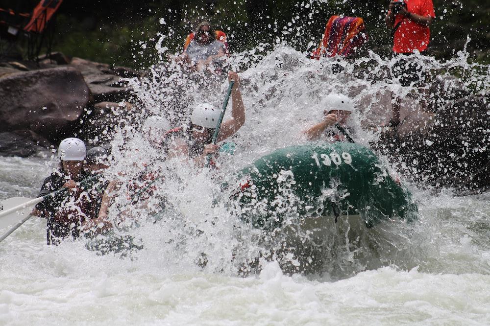 people in boat rowing raft