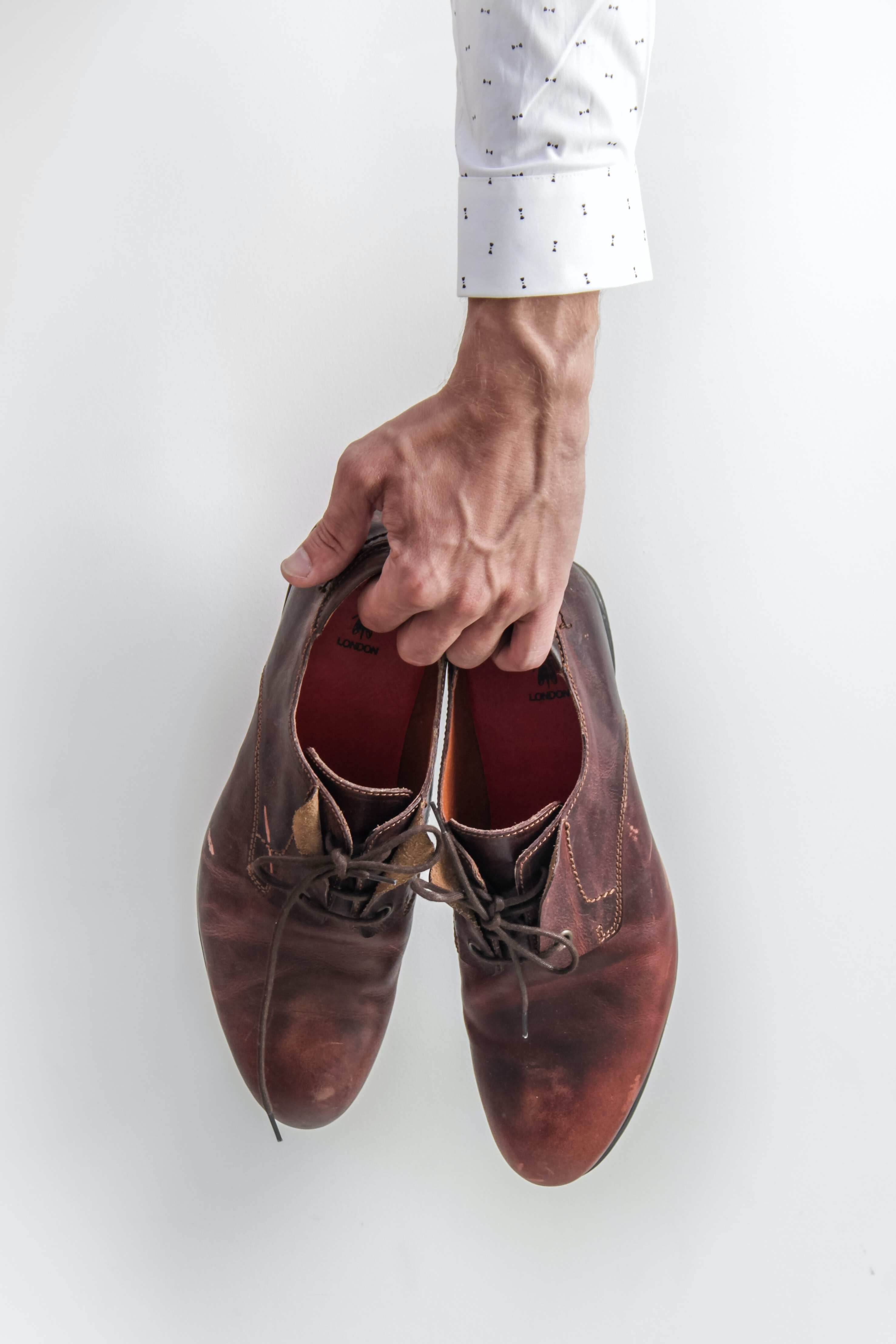 person holding pair of brown leather shoes
