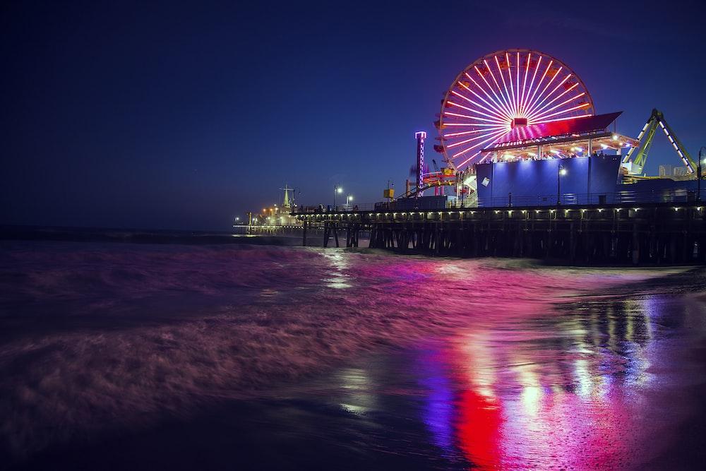photo of ferris wheel near body of water during nighttime