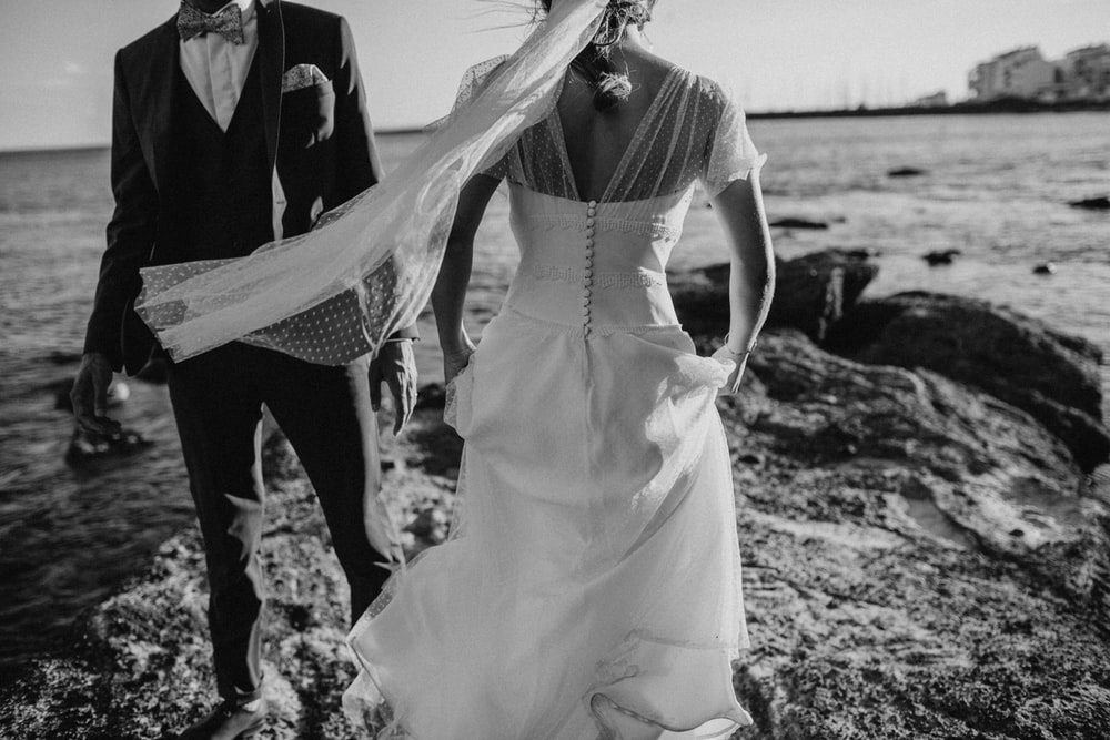 grayscale photography of groom and bridge on seashore during daytime