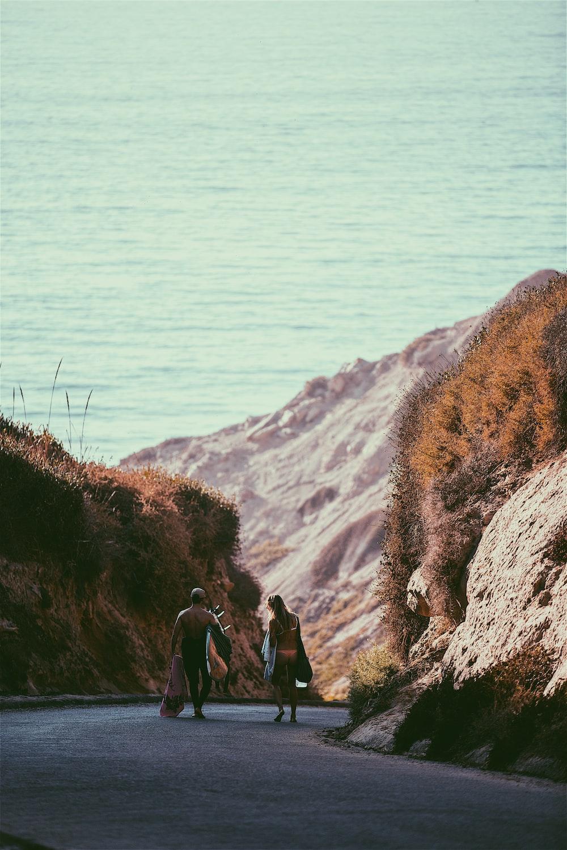 man and woman walking near rock formation