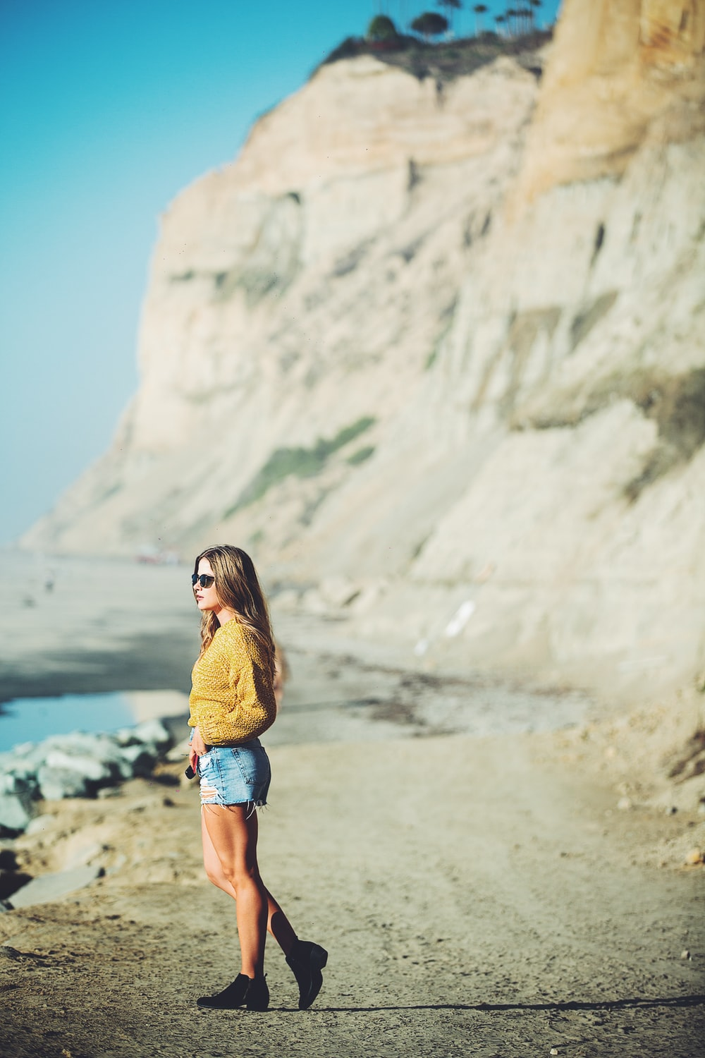 selective focus photo of woman standing near mountain