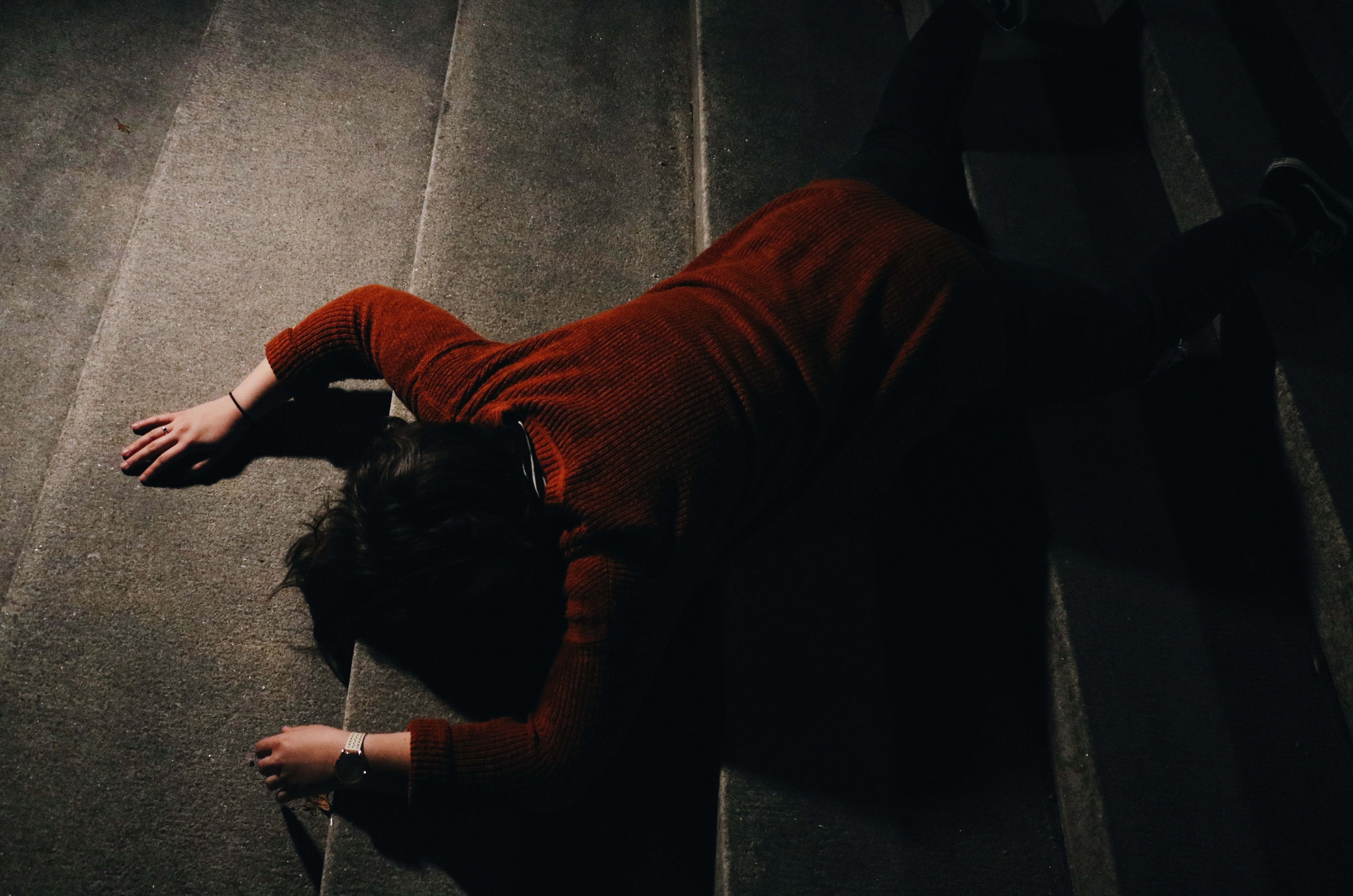 woman lying on stairway at nighttime