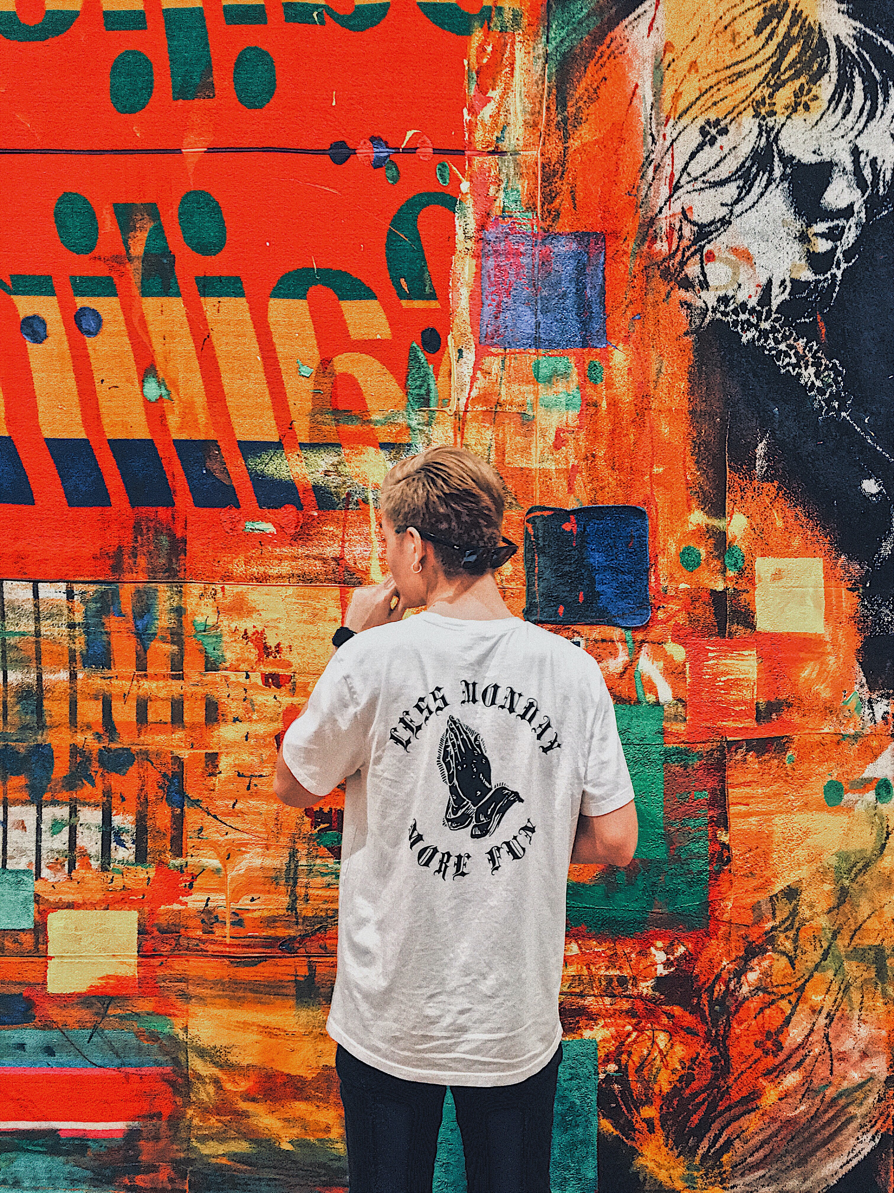 man holding his chin facing multicolored painted wall