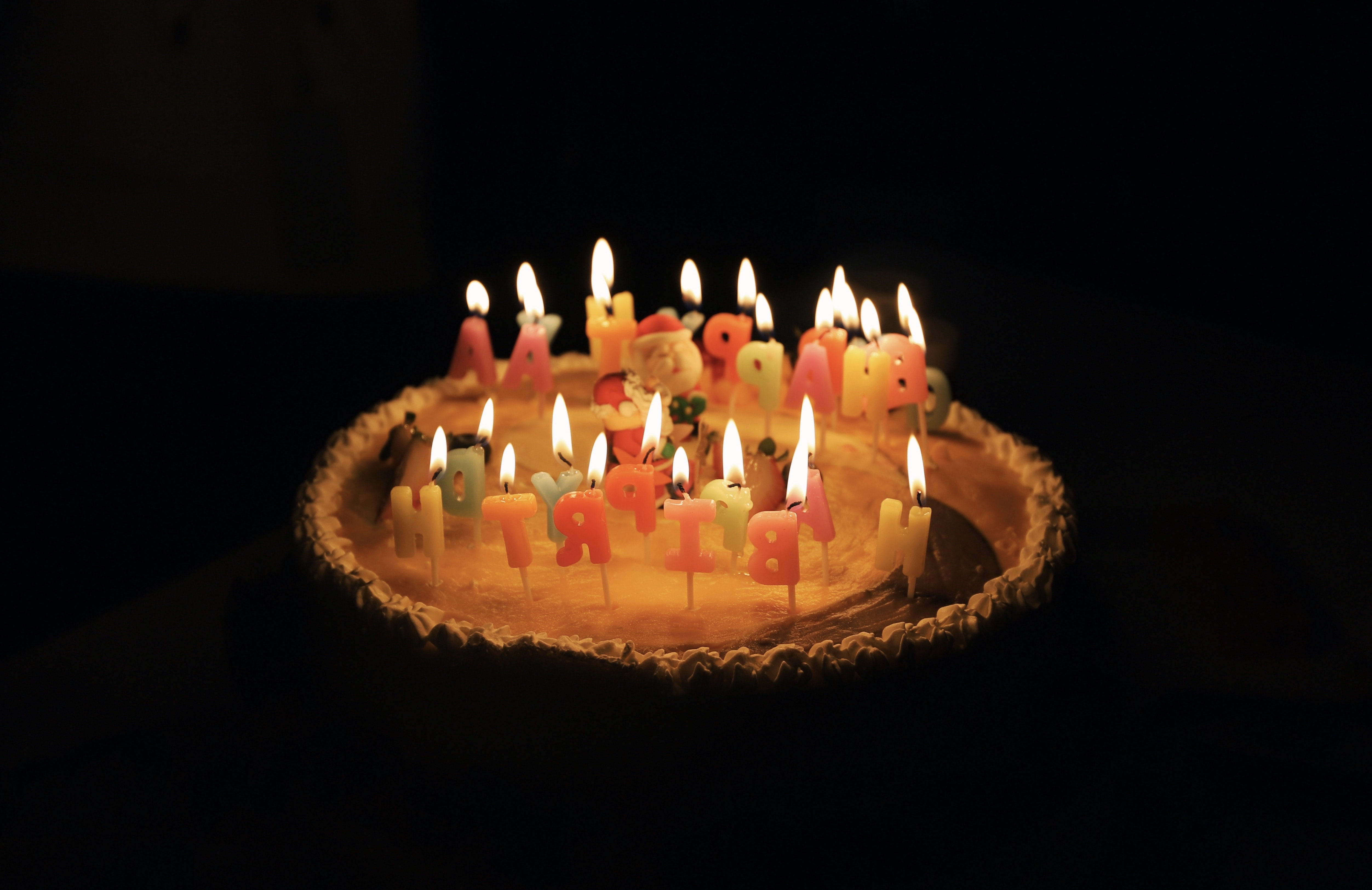 lighted assorted-color birthday candles in cake
