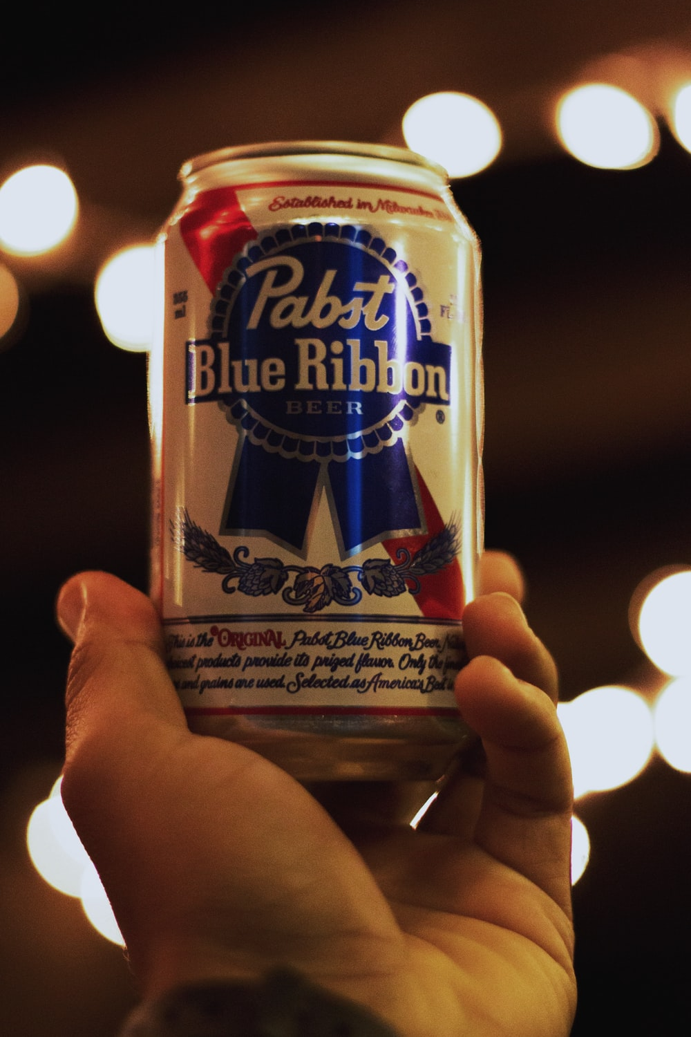 person holding a white and blue labeled can