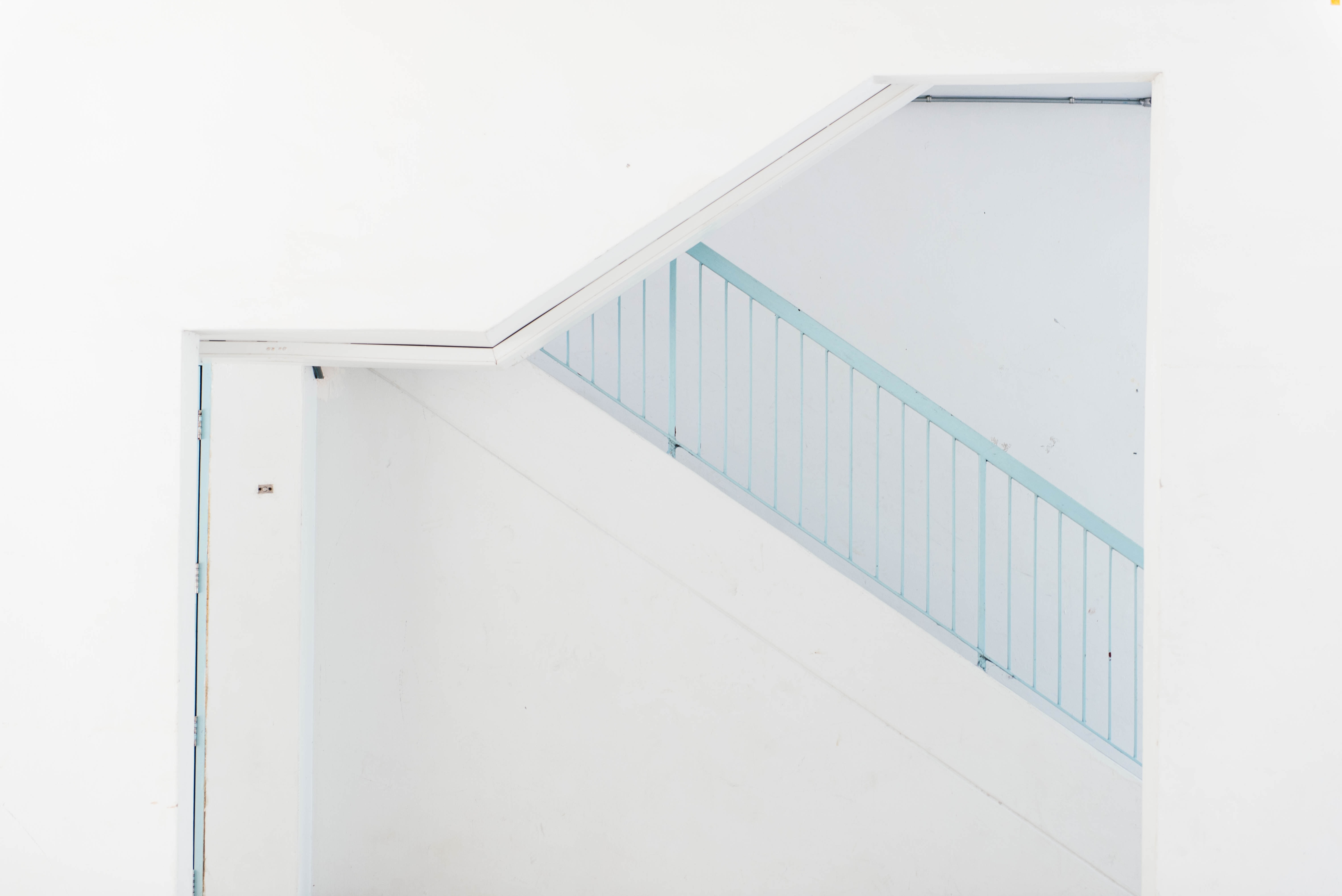 white wooden door beside blue stairs