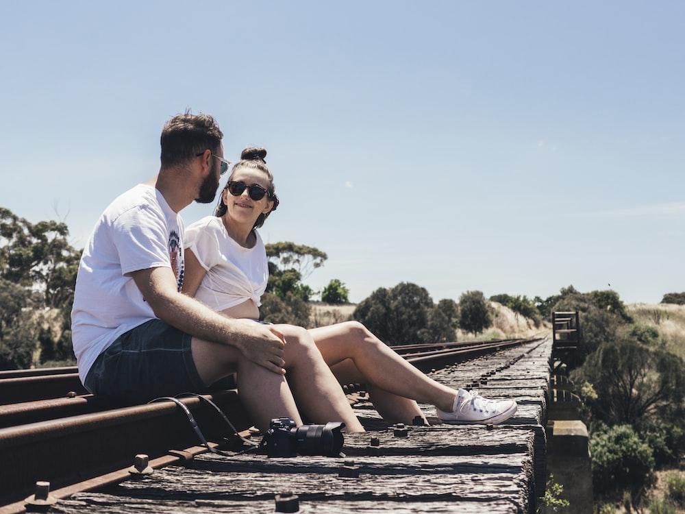 man and woman sitting on train rail