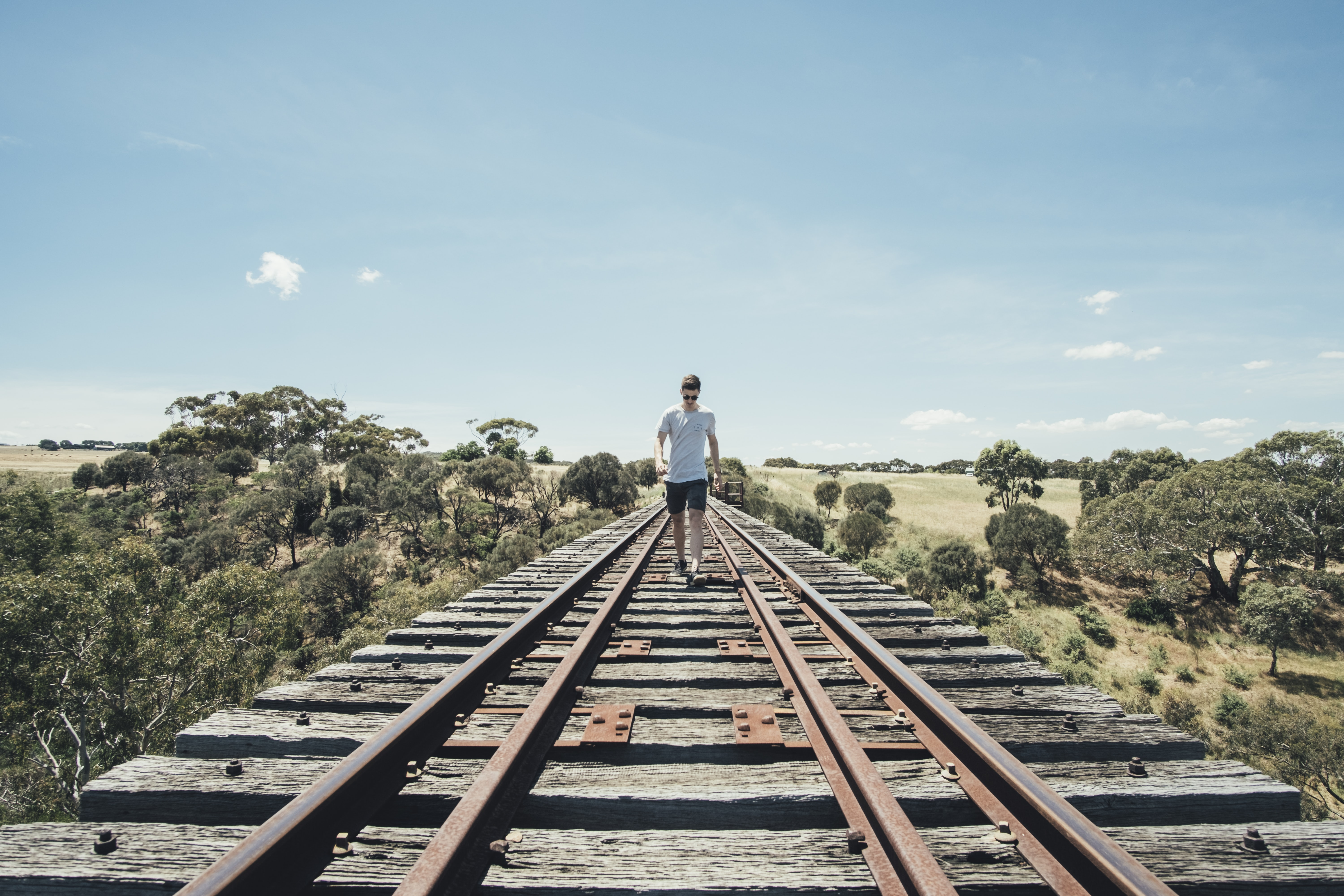 man walking on train rail track during day time