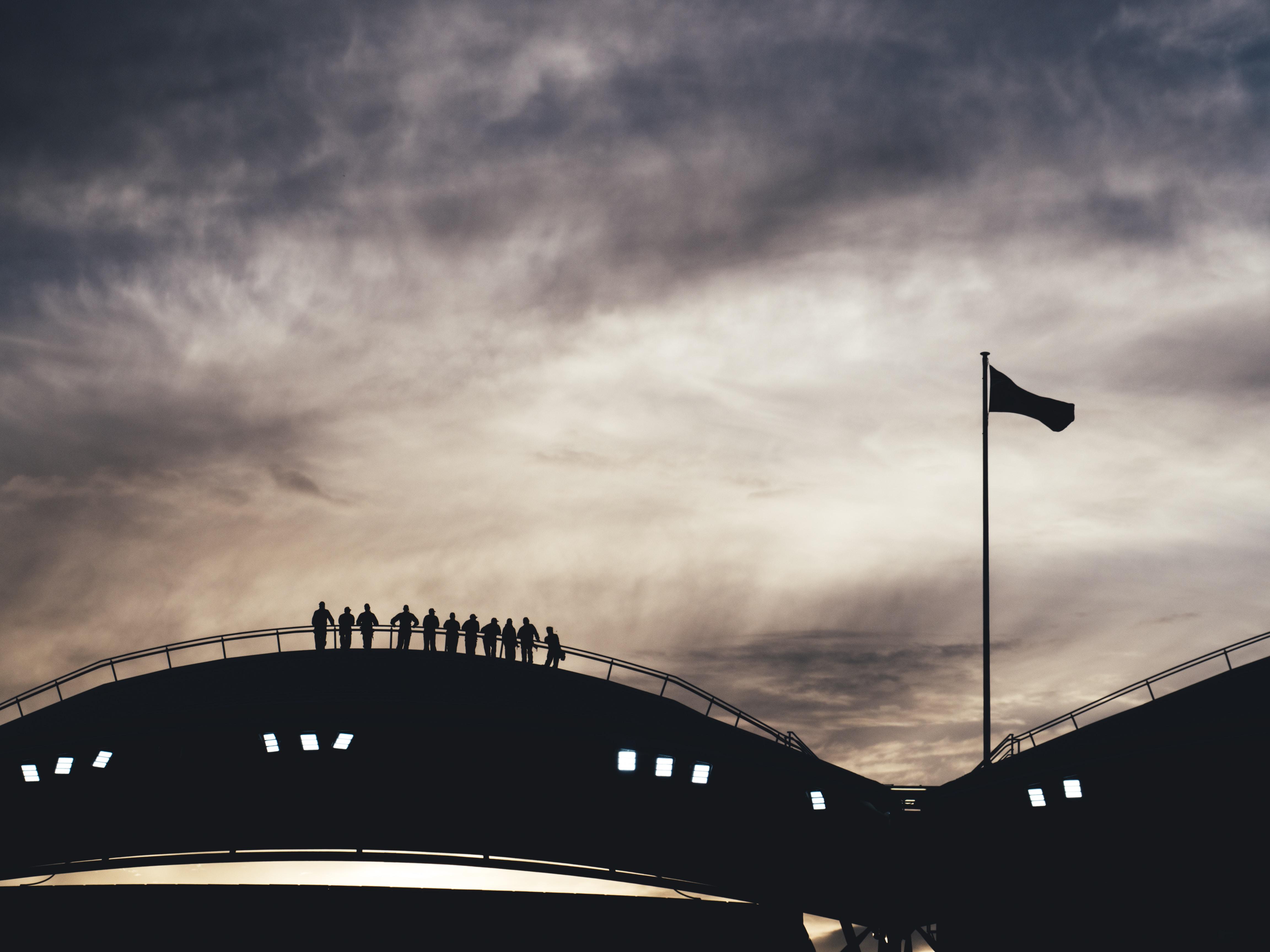 silhouette photo of people standing on bridge