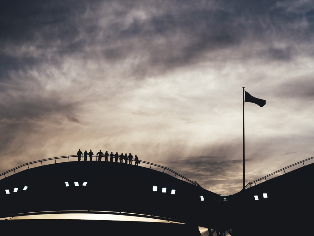 silhouette photo of people standing on bridge