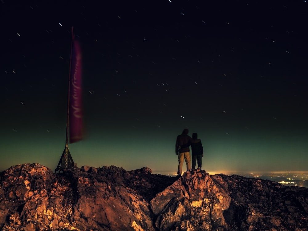 silhouette of two people standing on brown rocks under starry night