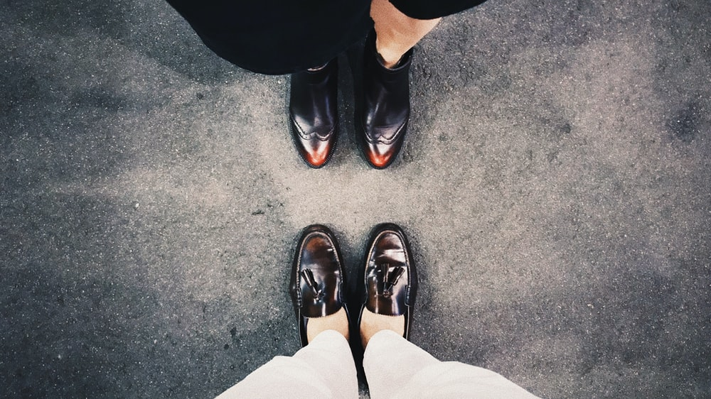 two person standing wearing black loafers