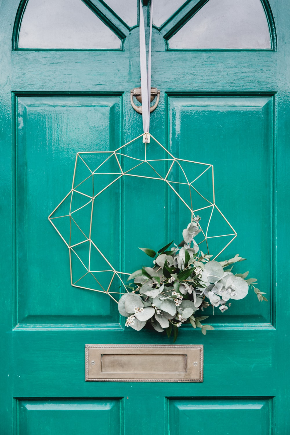 white hanging wreath on green door