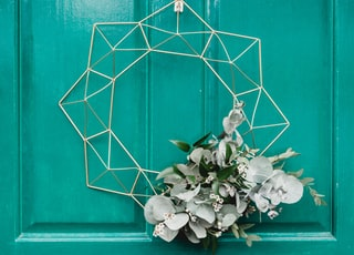 white hanging wreath on green door