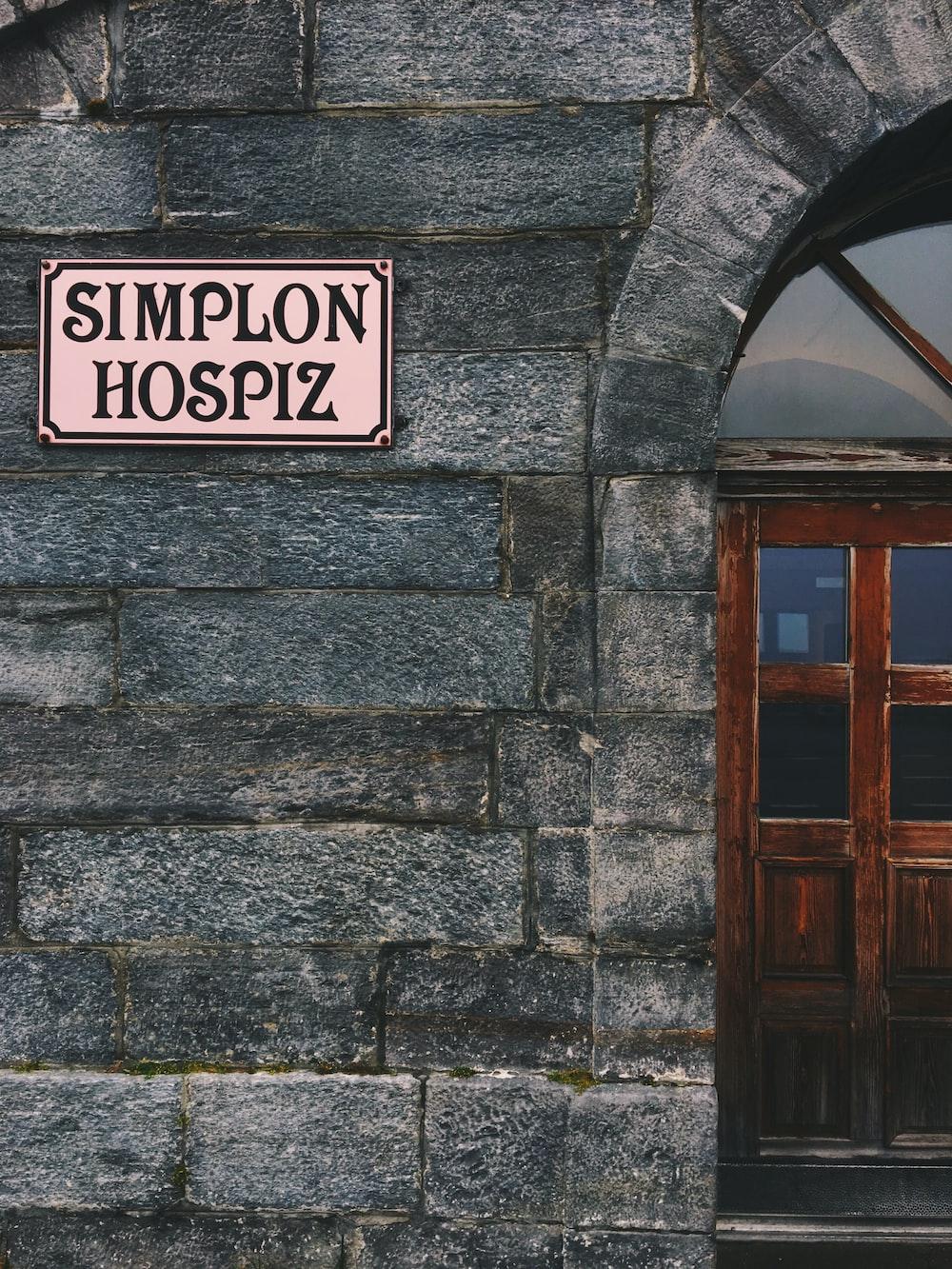 beige Simplon Hospiz signboard on wall