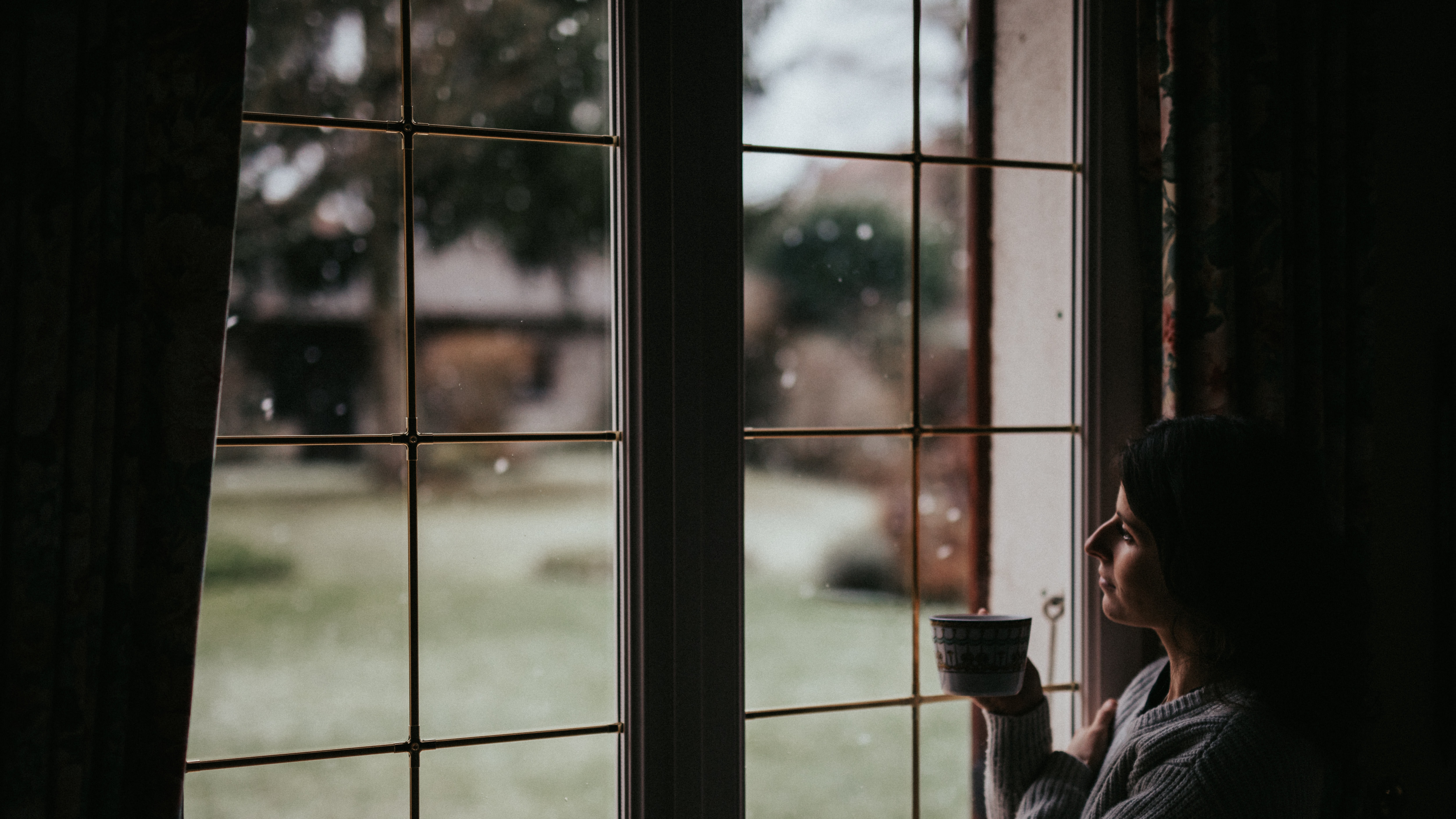 person holding mug while looking at window