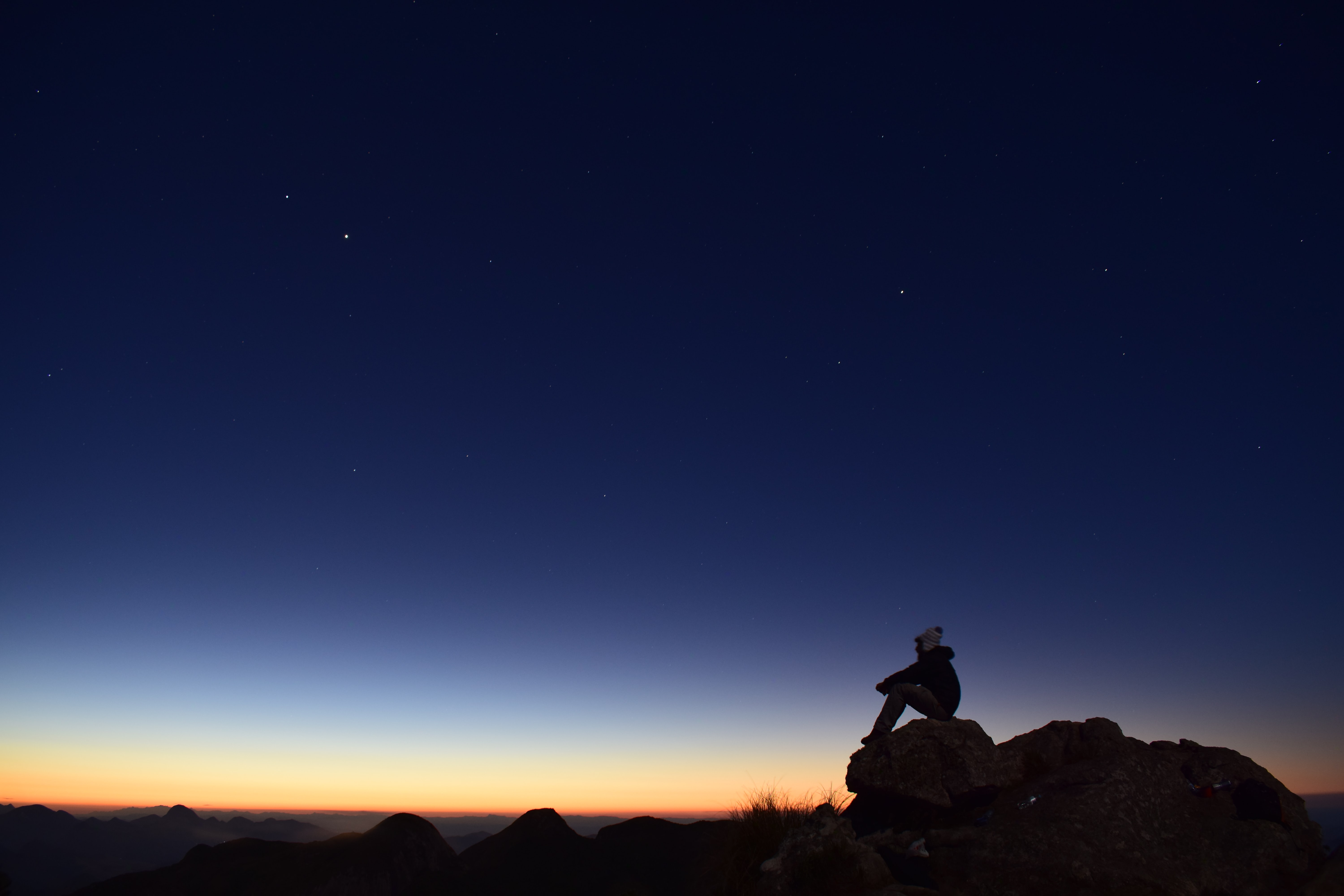 silhouette of person sitting on rock during night time