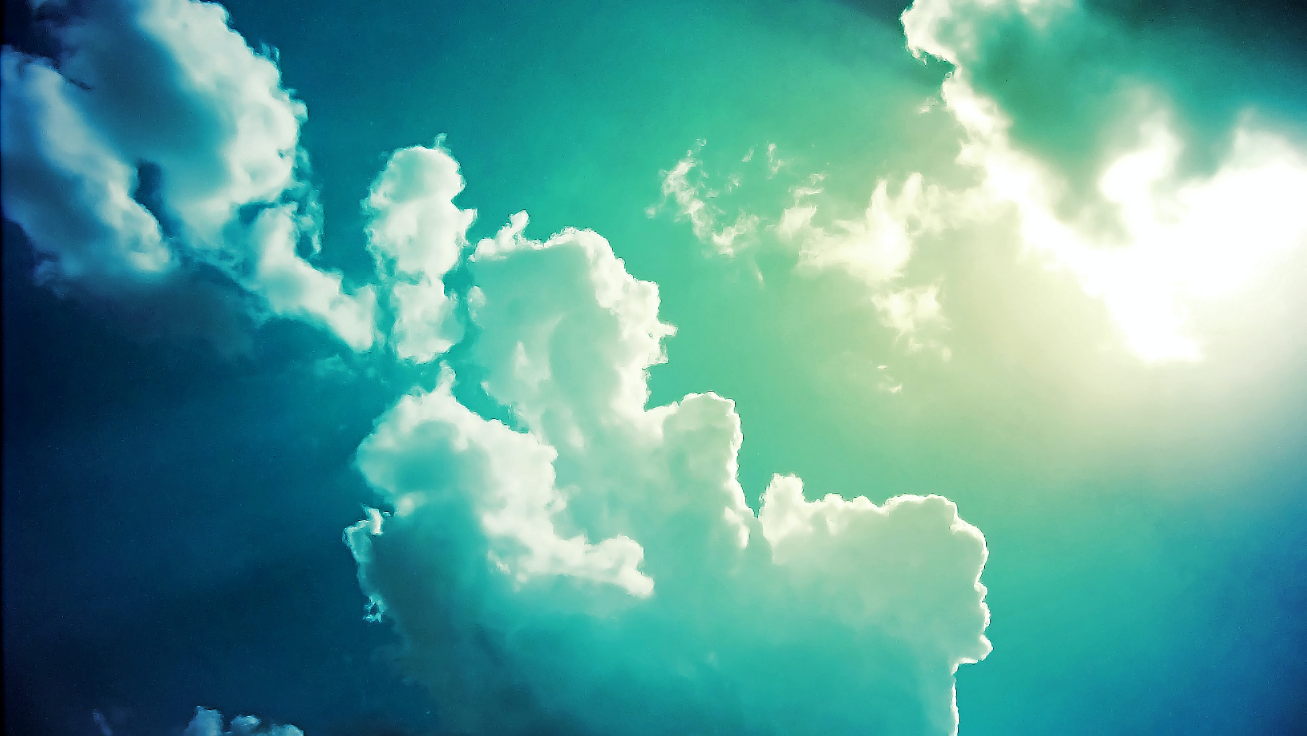 white clouds and blue skies with sunrays