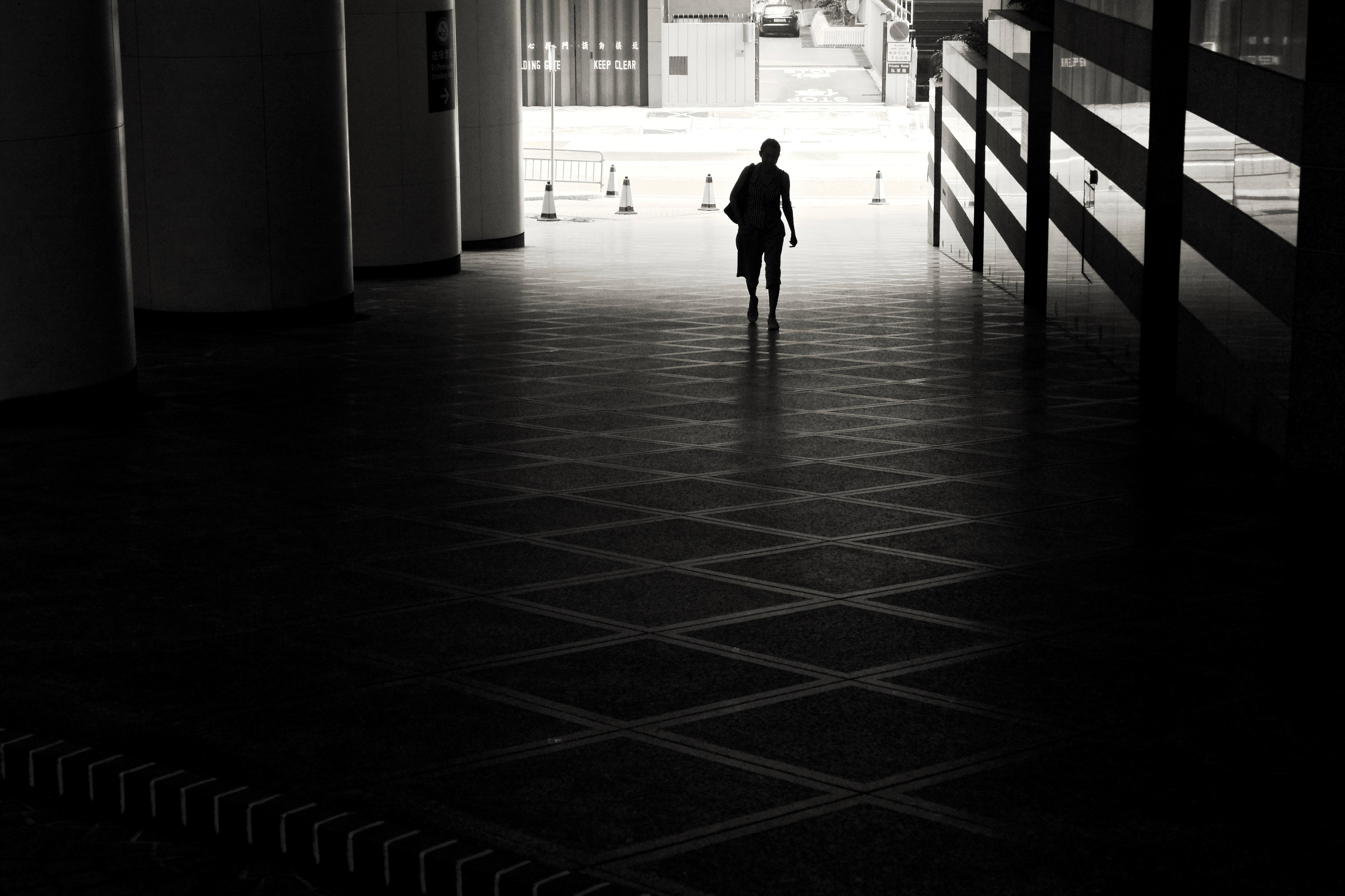 man walking on hallway taken during daytime