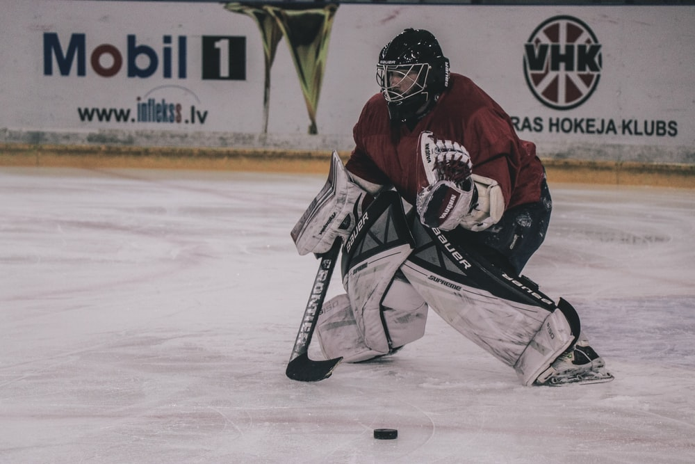 ice hockey player on court playing near mobil 1 and VHK painted wall